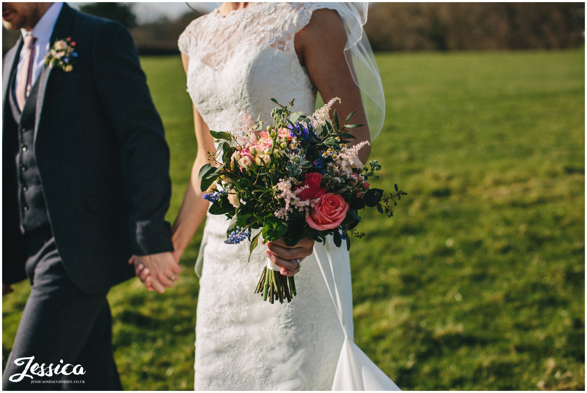 close up of bridal bouquet as she walks through a field with her husband - tower hill barns wedding photography