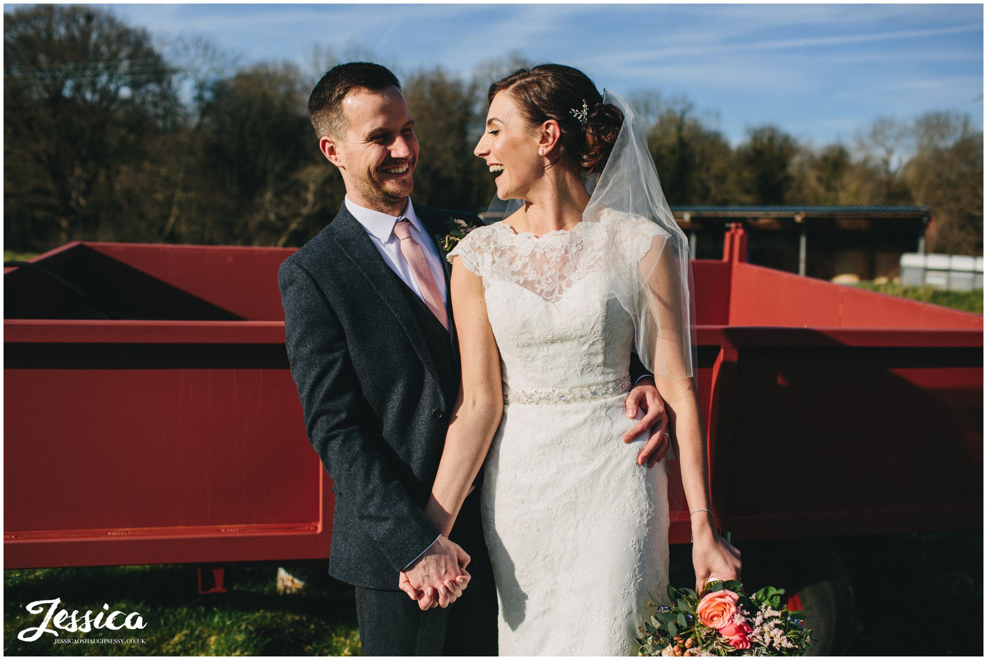 couple laugh in the sun with farm equipment behind them