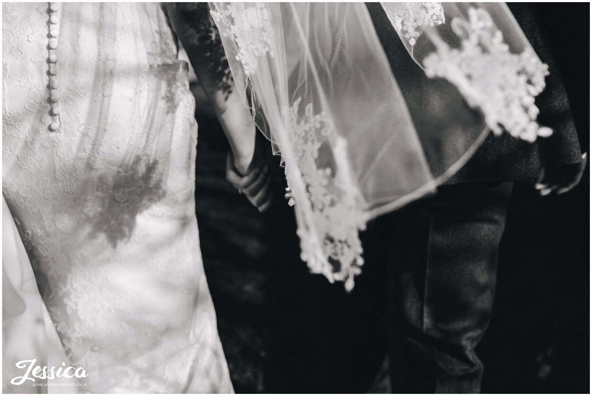 detail shot of the brides veil as she holds grooms hand