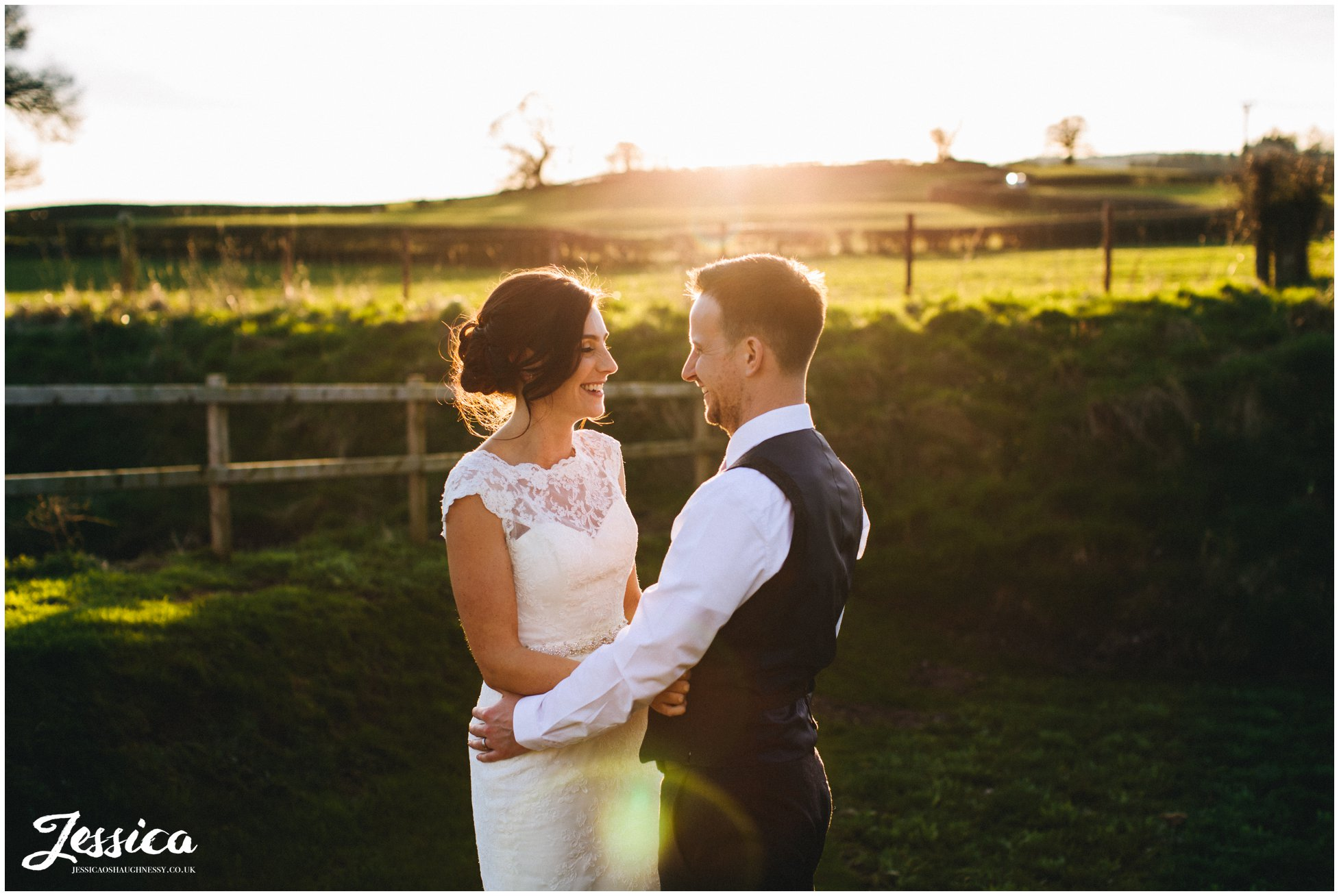 bride & groom laugh in the sunlight on the evening of their wedding day in north wales
