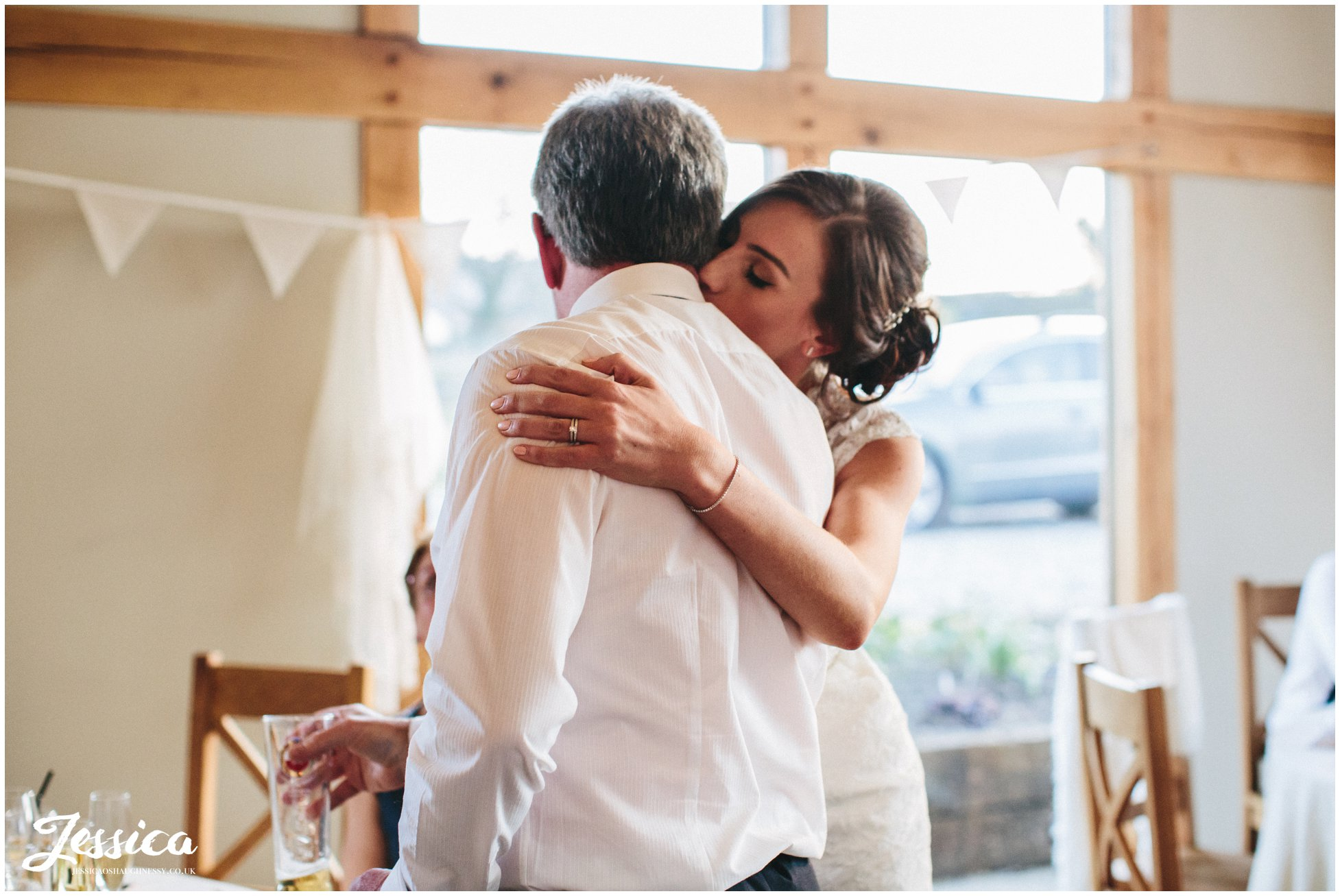 bride hugs her father after his speech on her wedding day in north wales