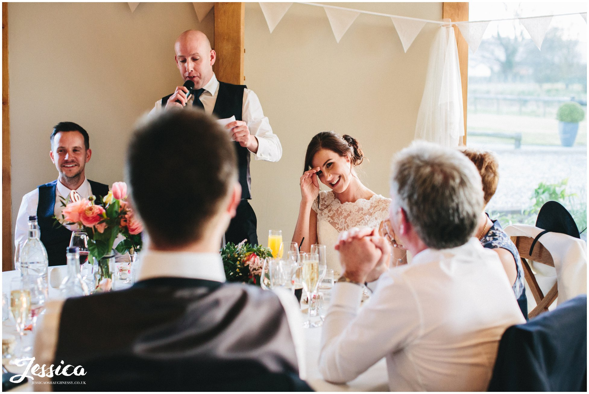 bride hides face during the best mans speech