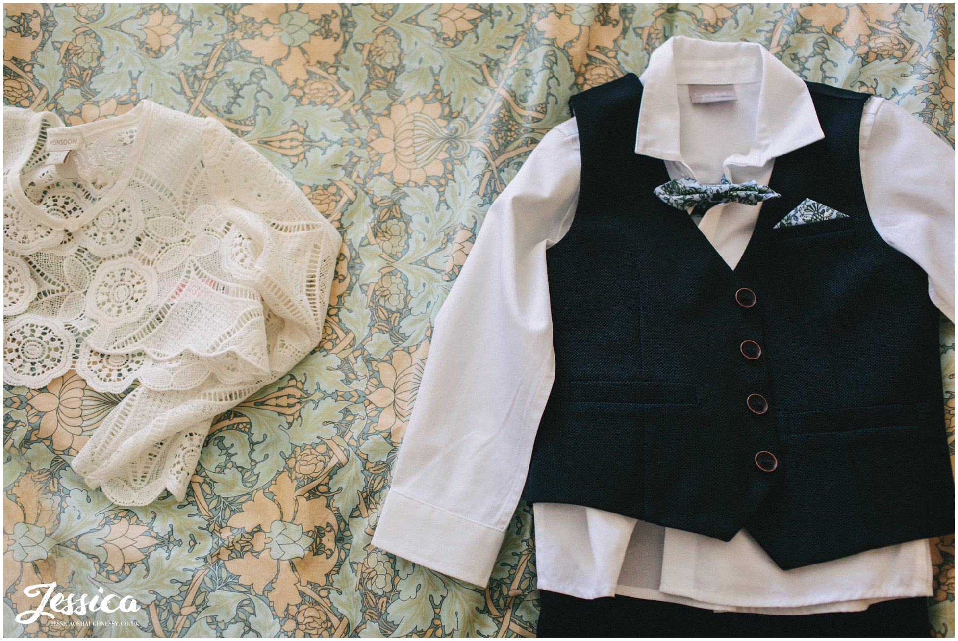 child's wedding outfit laid out on the bed