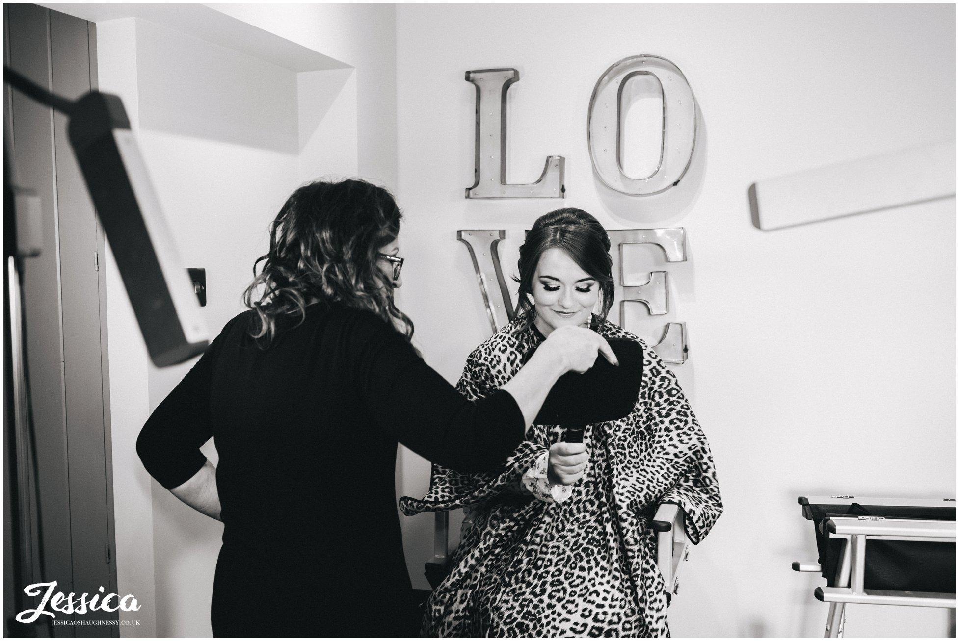 make up artist shows bride her finished makeup