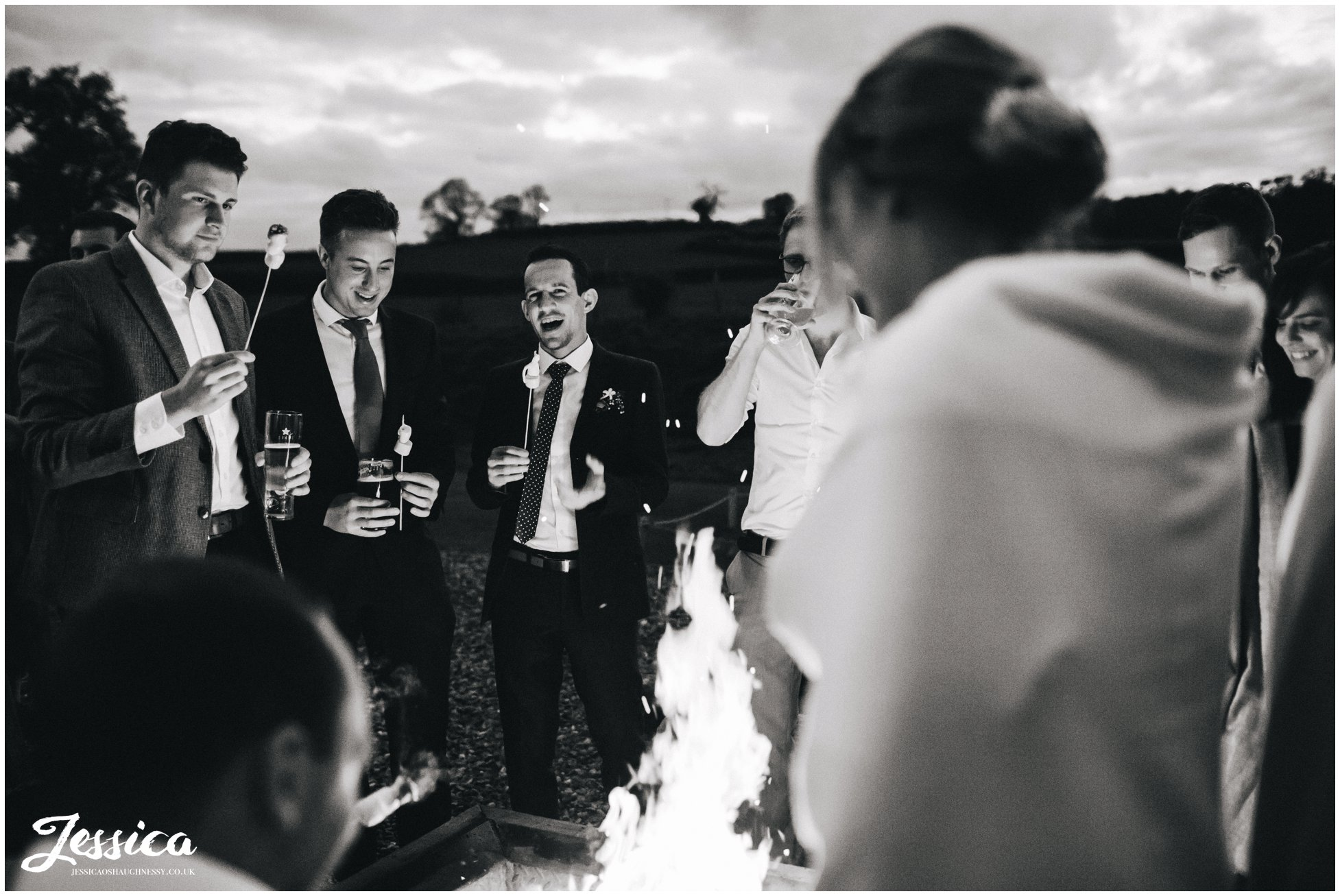 guests toast marshmallows round the fire