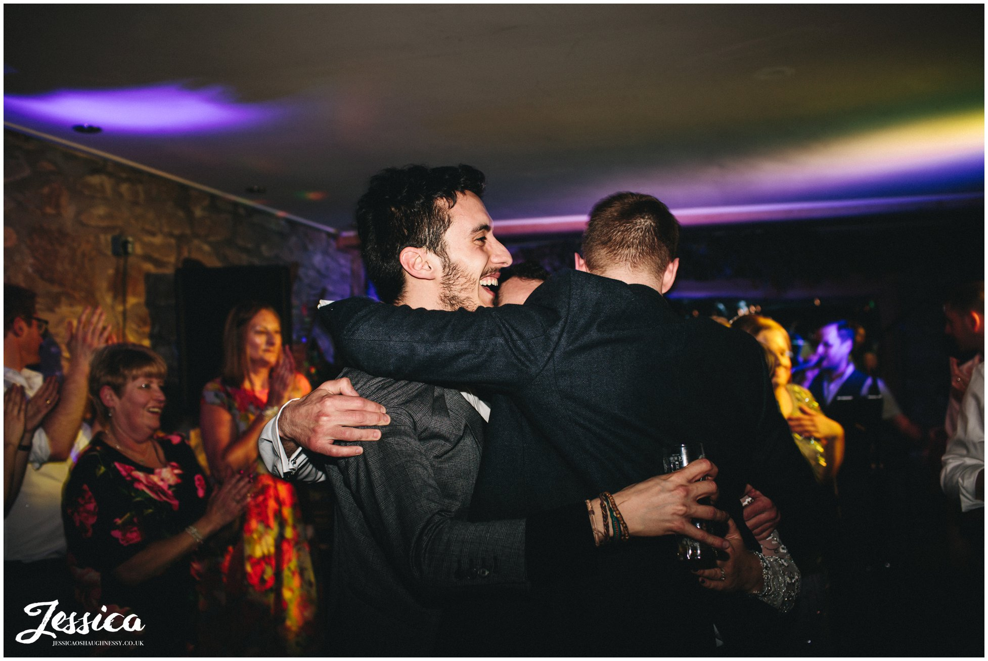 guest hugs the groom on the dancefloor at tower hill barns in wrexham