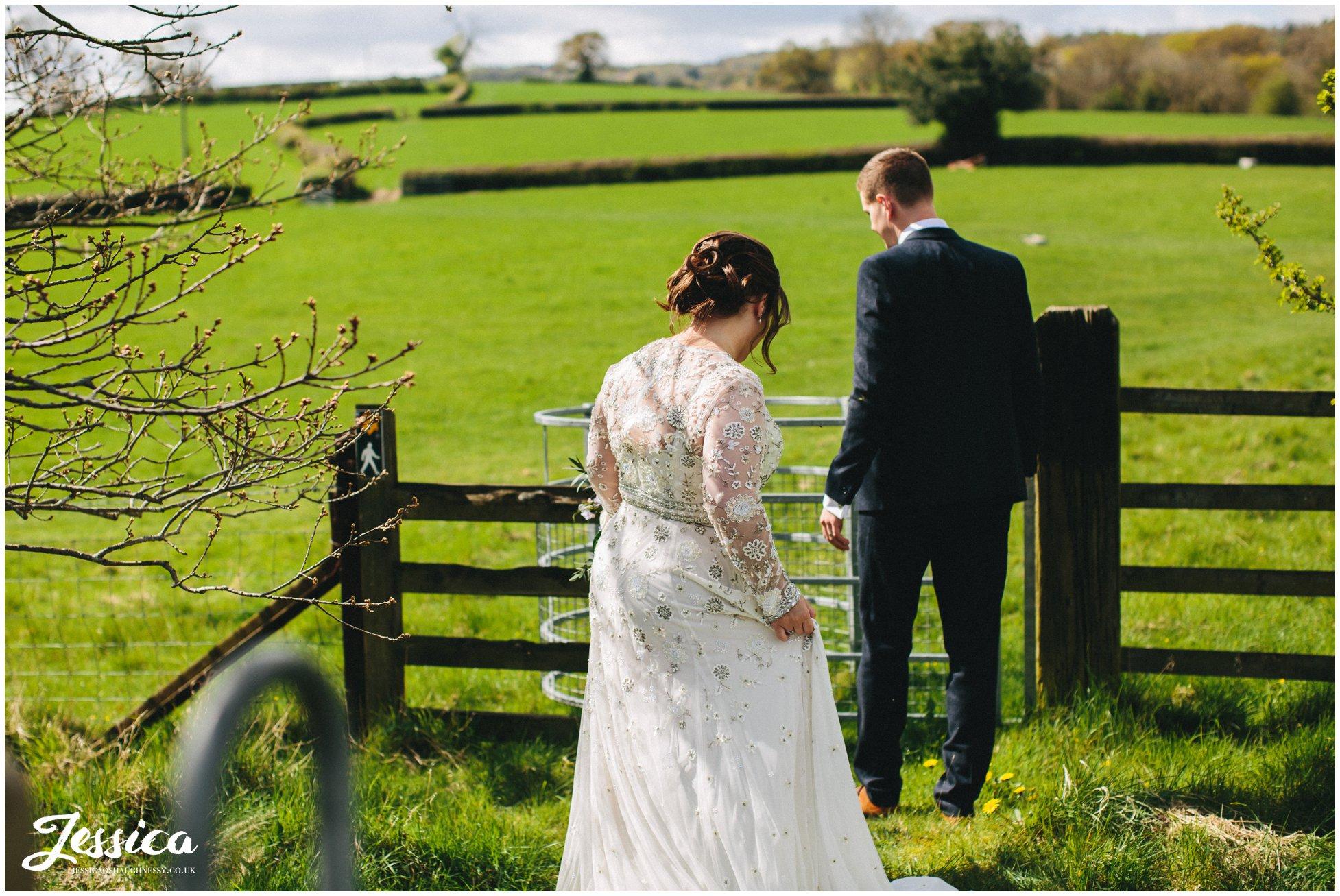 newly wed's walk through gates into field