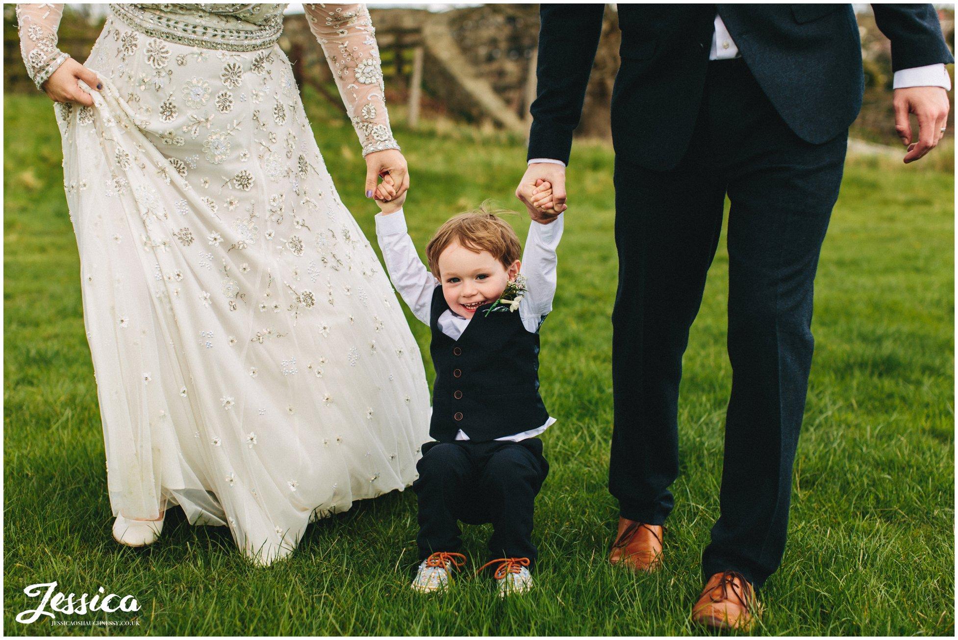child holds parents hands at a wedding in trevor, wrexham