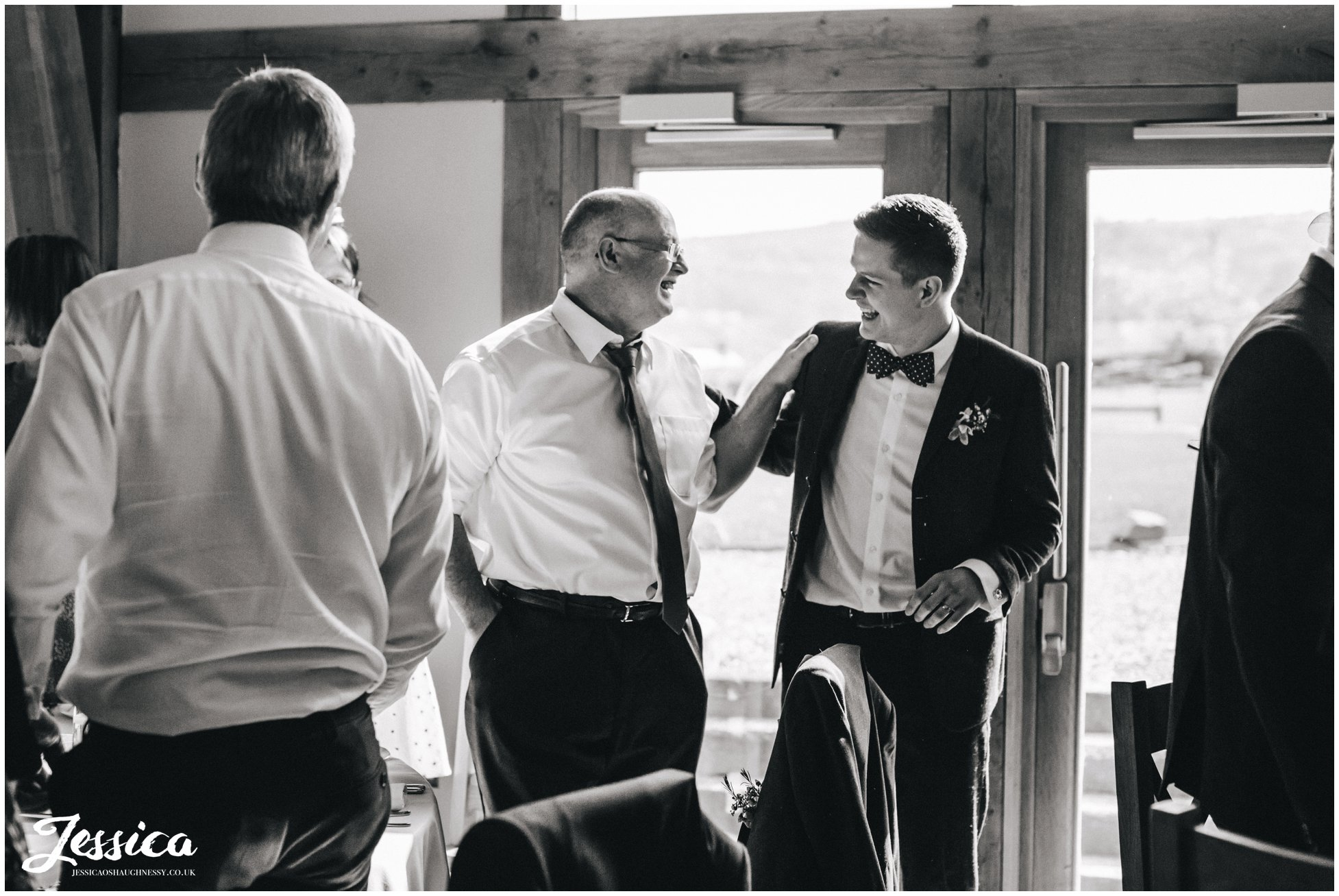 groom & his father laughing in the new barn, north wales