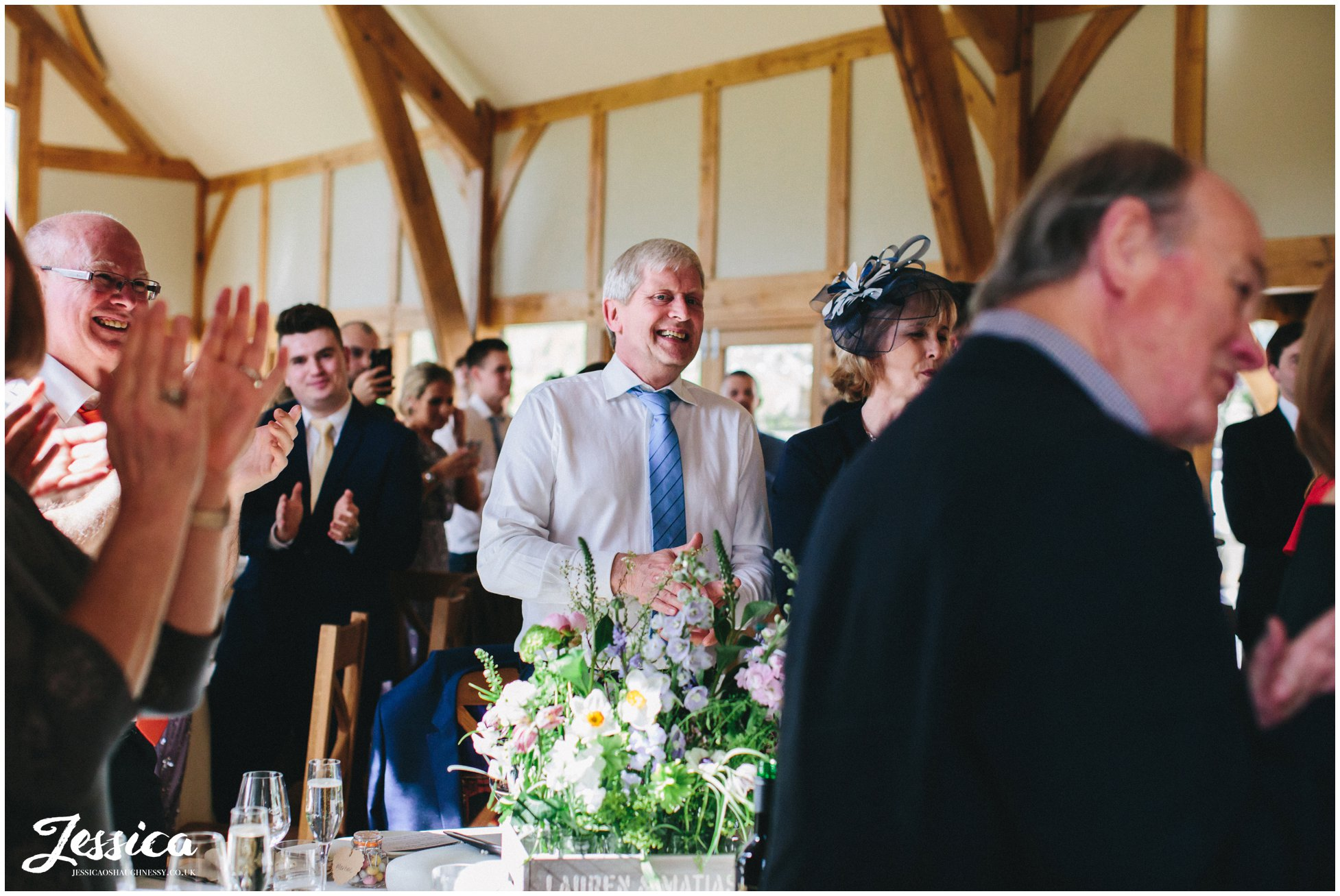 guests clapping as bride & groom enter the room