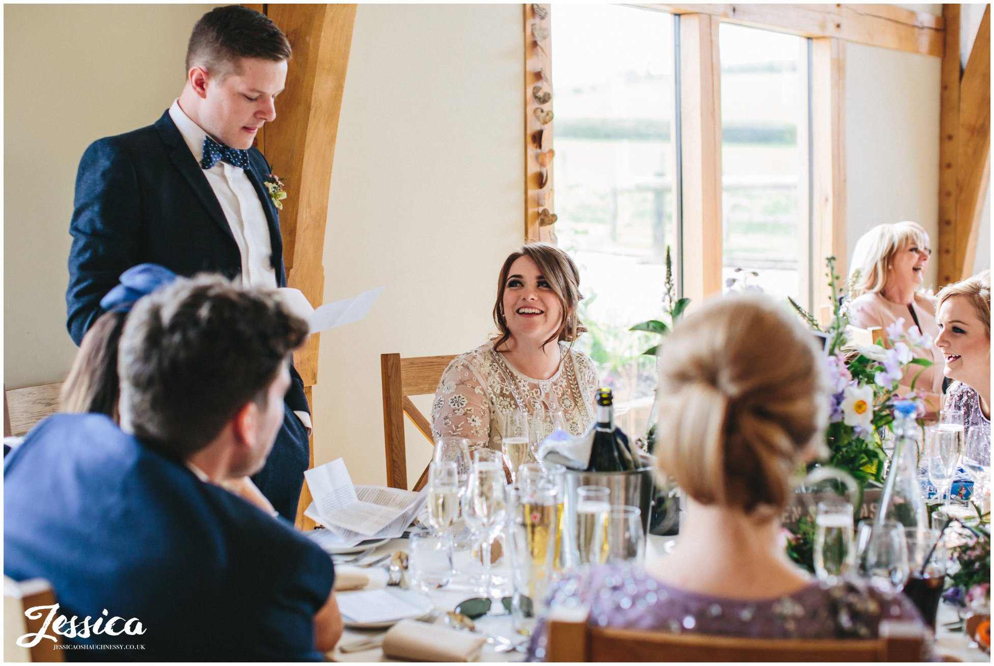 bride smiles at groom during his speech
