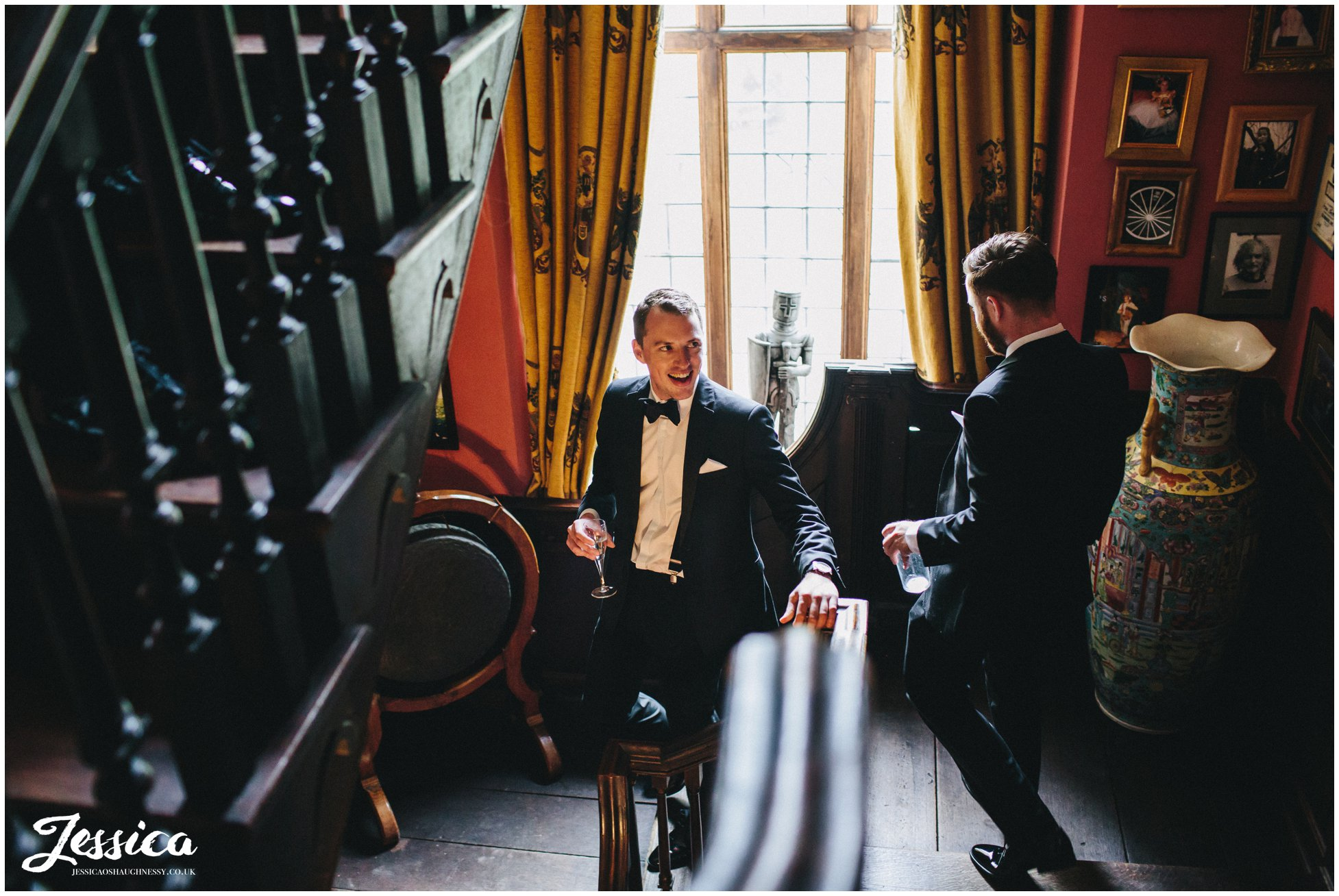 groom heads downstairs drinking champagne before the wedding ceremony