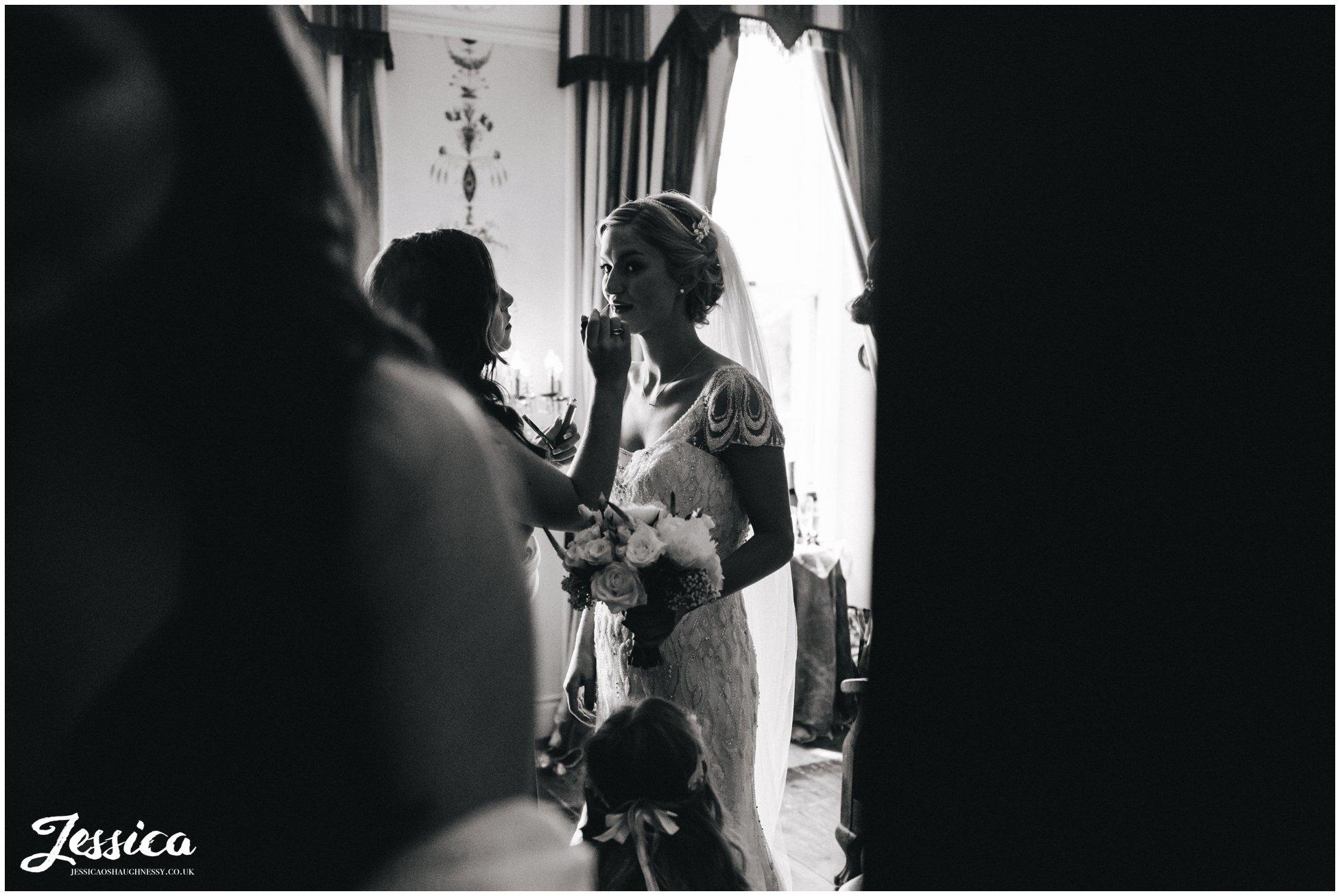 bride puts on lipstick ahead of the ceremony