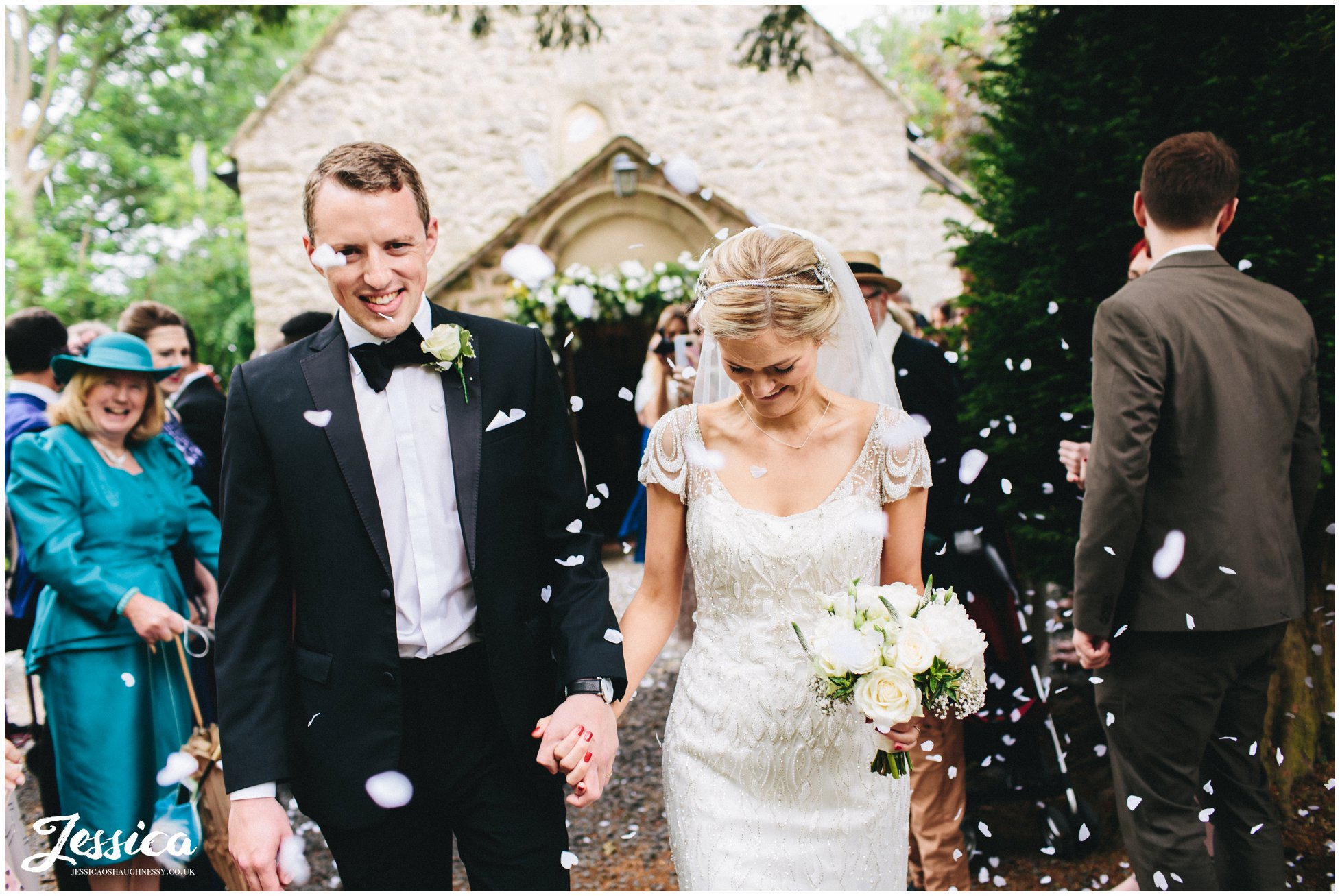 newly wed's walk through confetti line after their ceremony in Trevor, North Wales