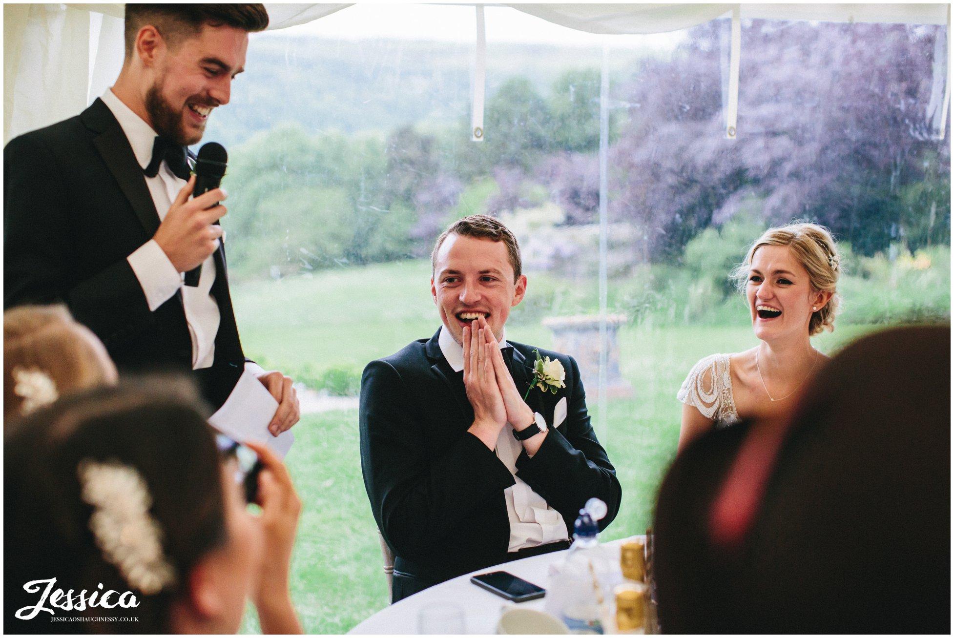 groom looks shocked during the best man's speech
