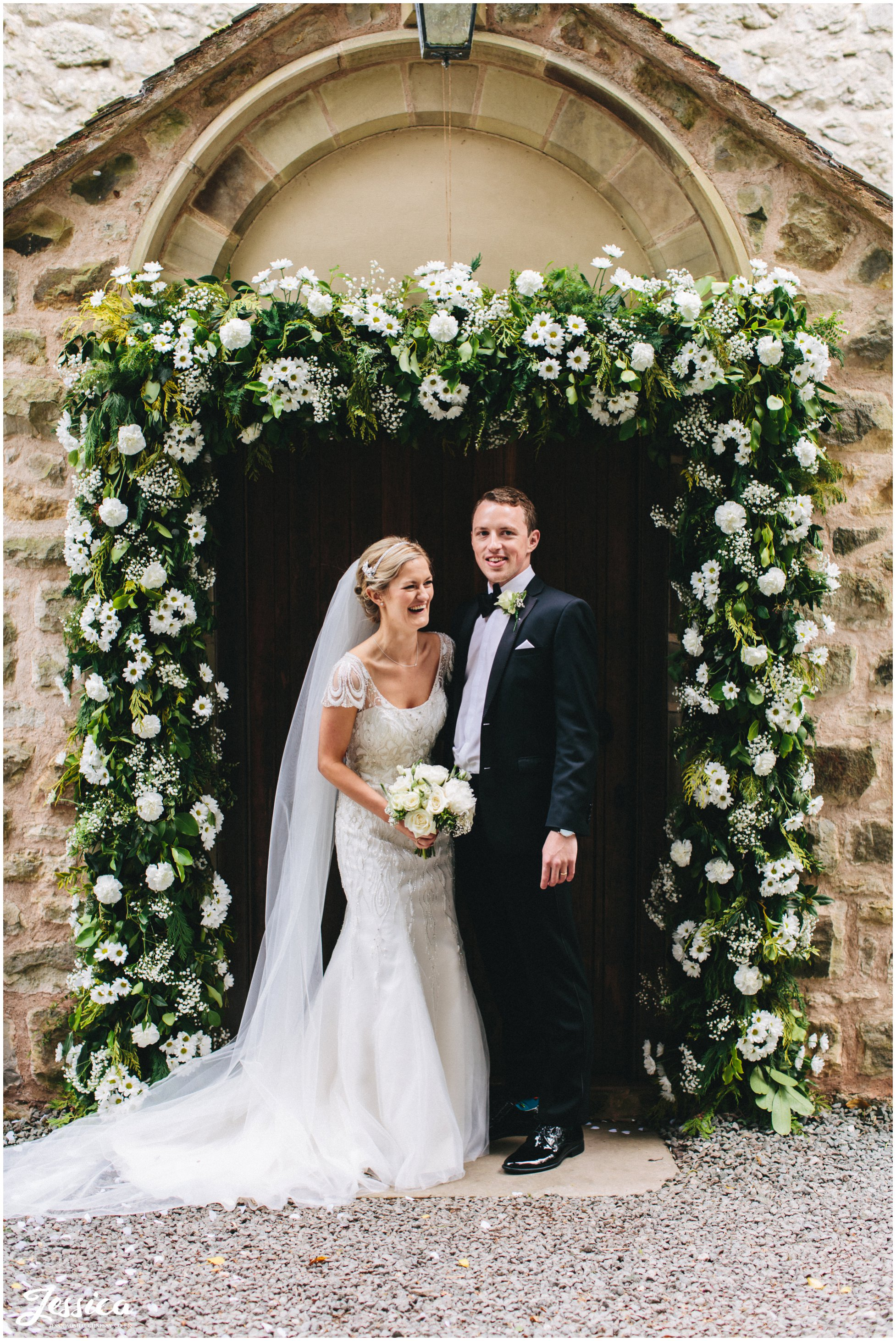 bride & groom stand under their floral arch in Trevor, North Wales