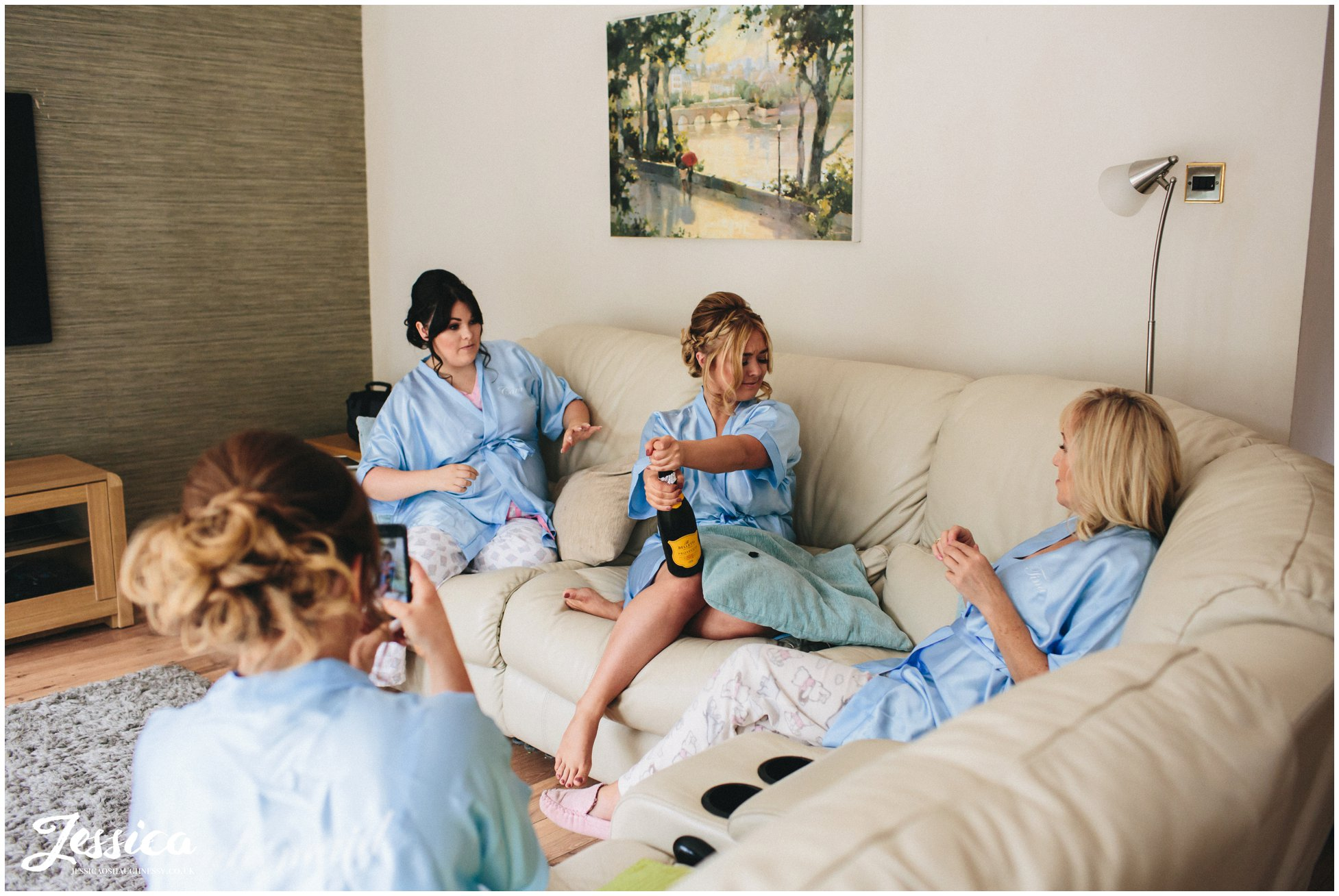 bridemaids open champagne on the morning of the wedding