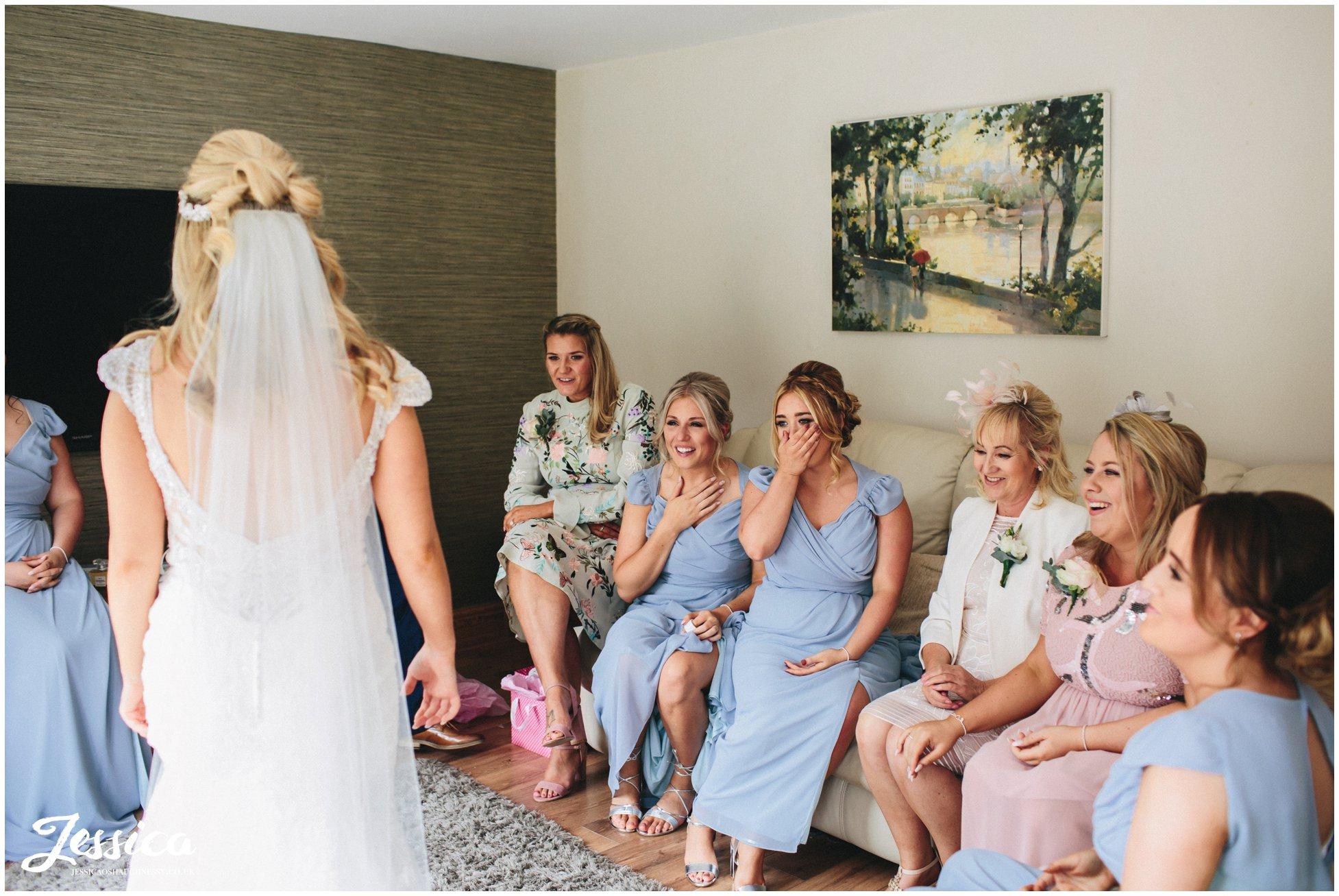 bridesmaids gasp at bride in her wedding dress