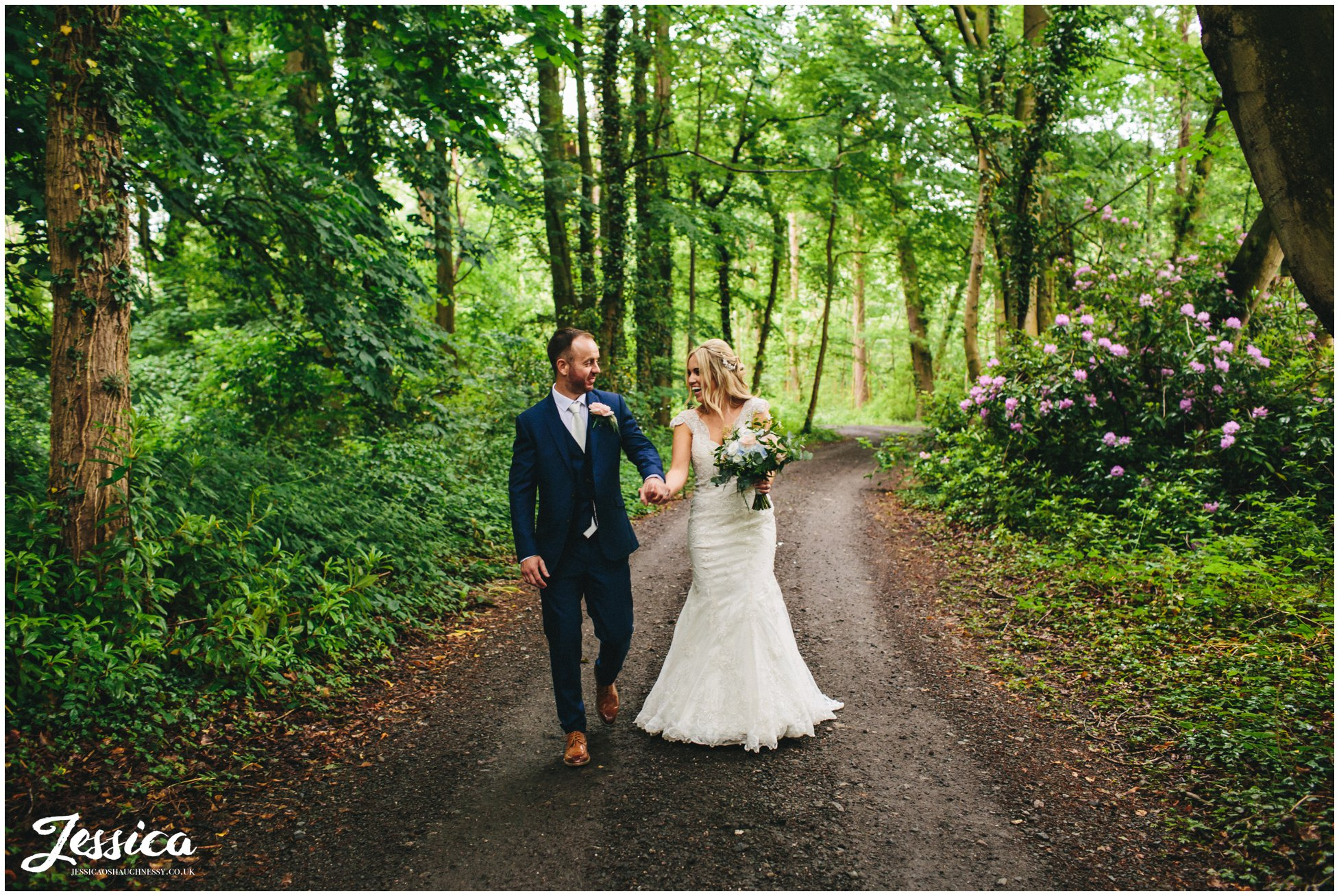 bride & groom walk through woodland at thornton manor, wirral
