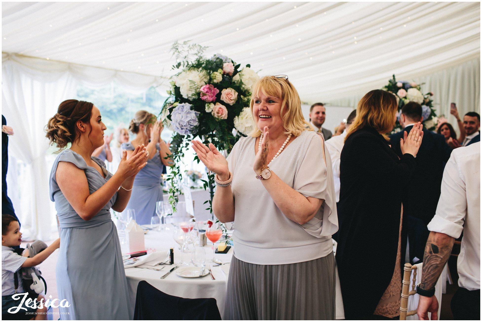 guests aplaude bride & groom walking into wedding room