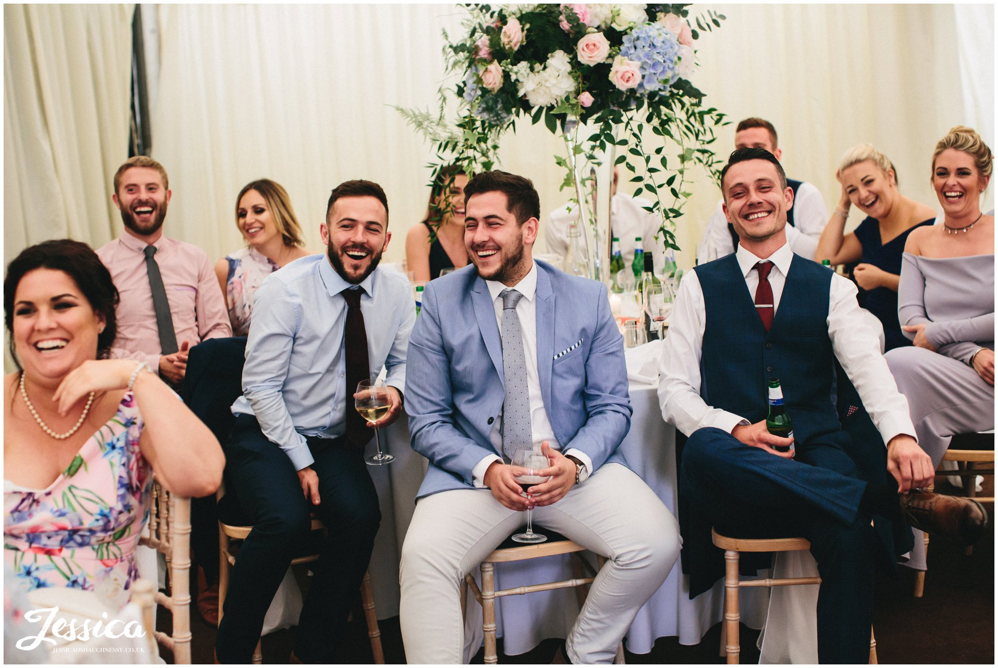 newly wed's friends laughing during the speeches