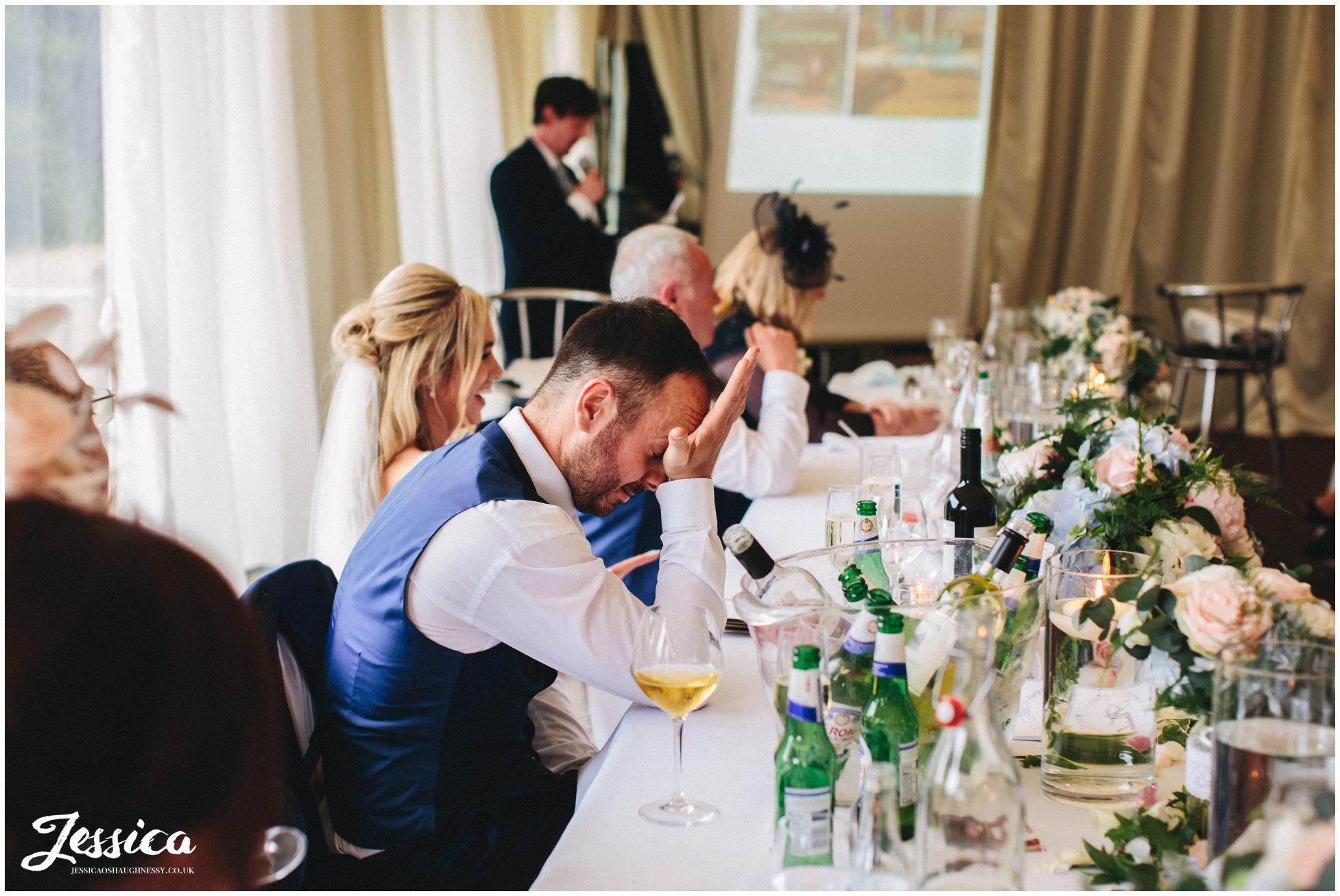 groom looking embarrassed during best man's speech