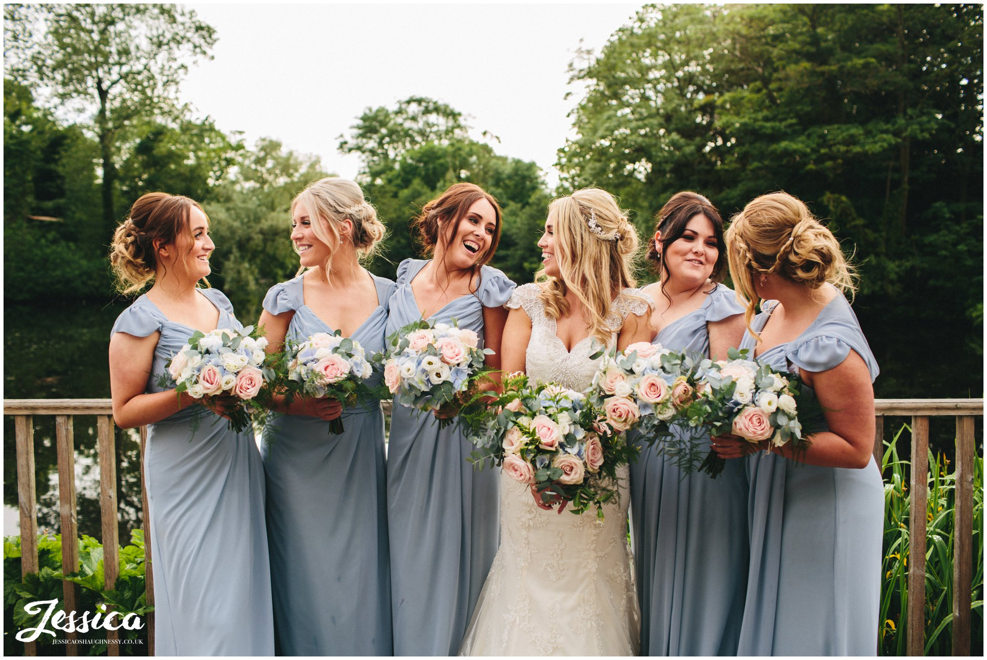 bridesmaids pose in front of lake at thornton manor, on the wirral