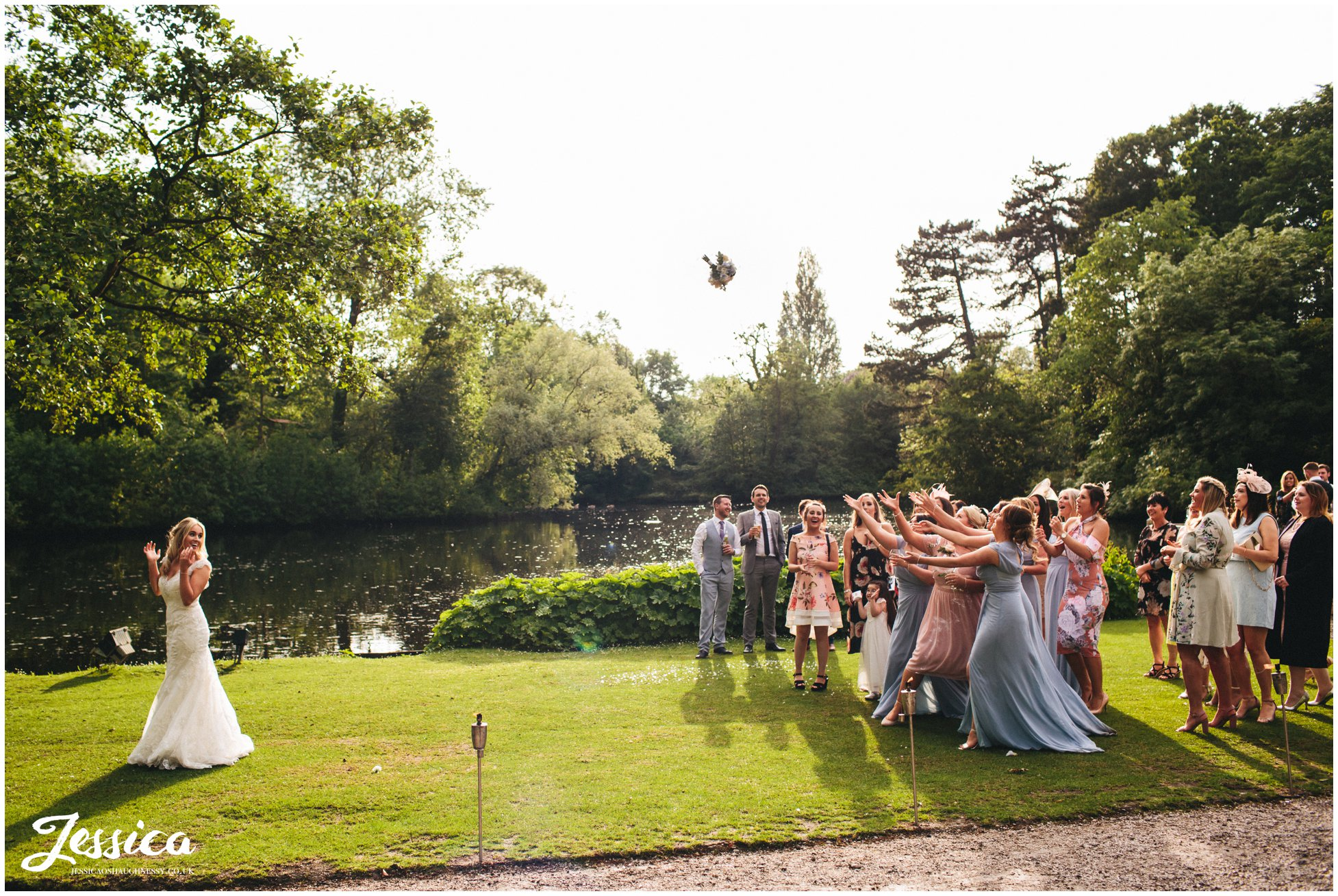 bride throws her bouquet by the lake - wirral wedding photography