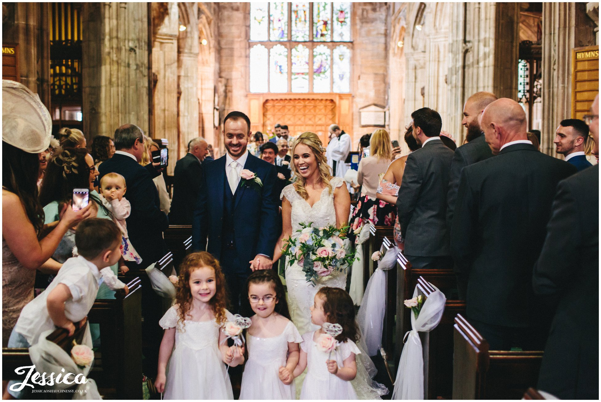 bride, groom & flower girls exit church after their ceremony