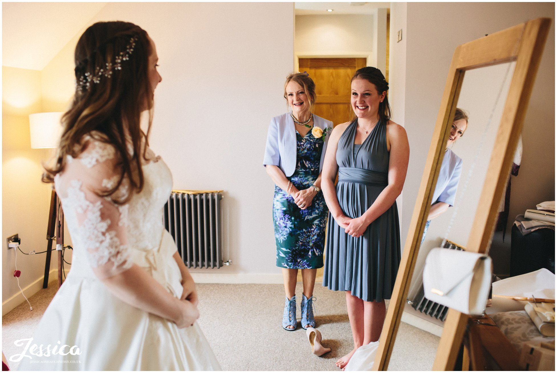 mother and sister of the bride admire her in her wedding dress