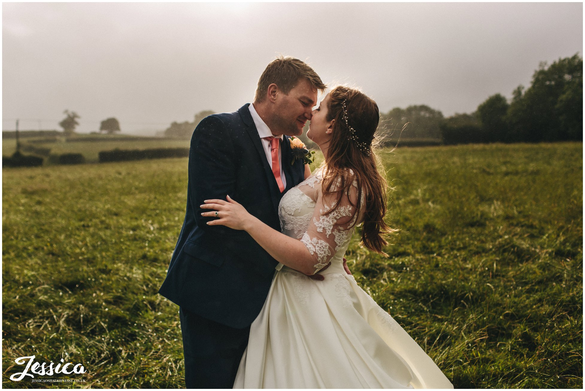 bride & groom kiss in the rain, in the middle of a windy field