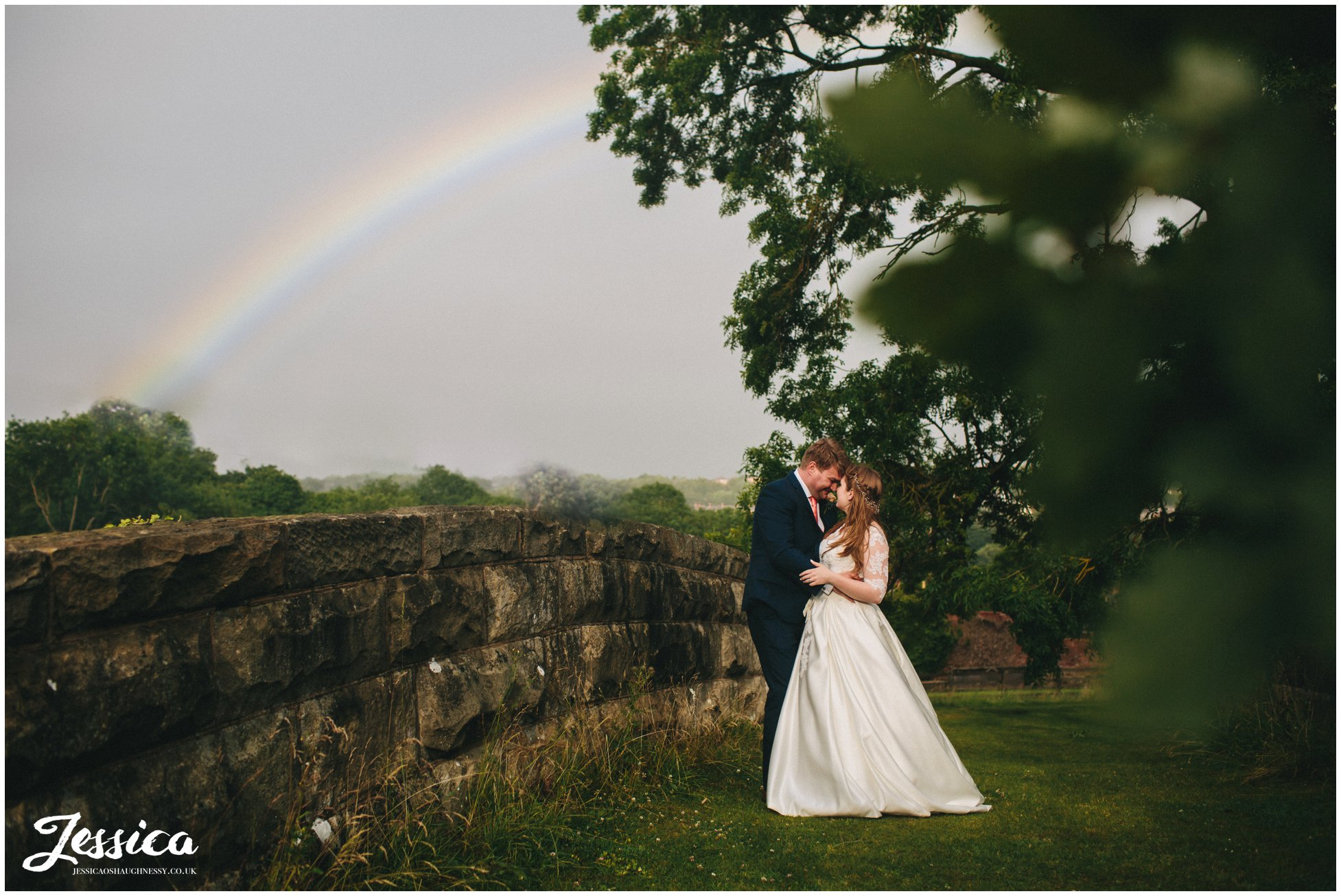 bride & groom stand under a rainbow that appeared over tower hill barns