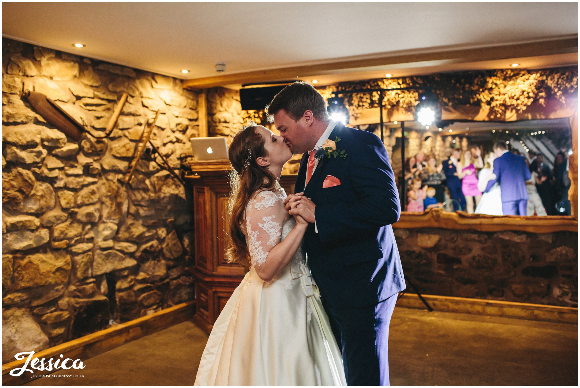 bride & groom kiss during their first dance in the old barn