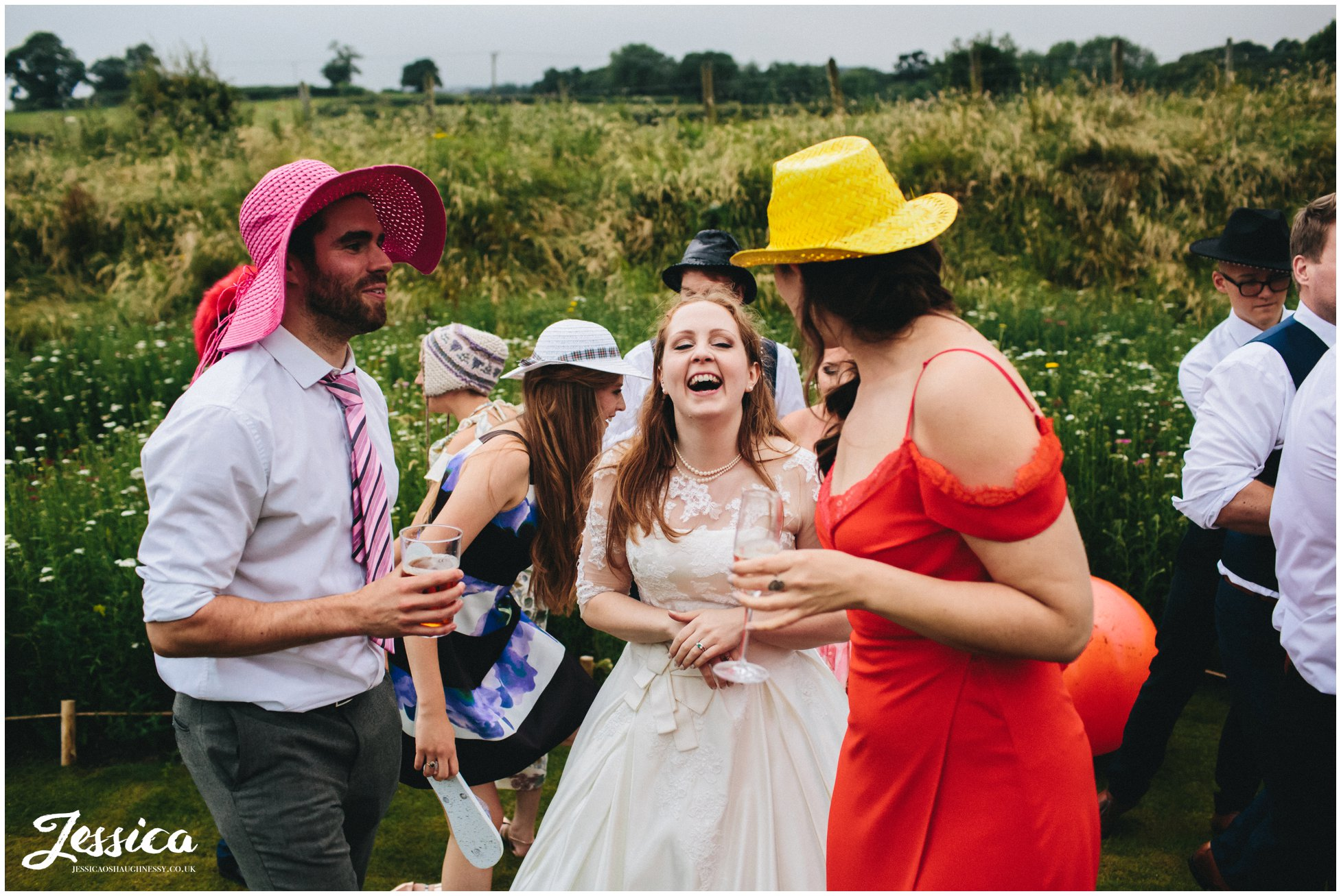 bride laughs at friends wearing props at tower hill barns