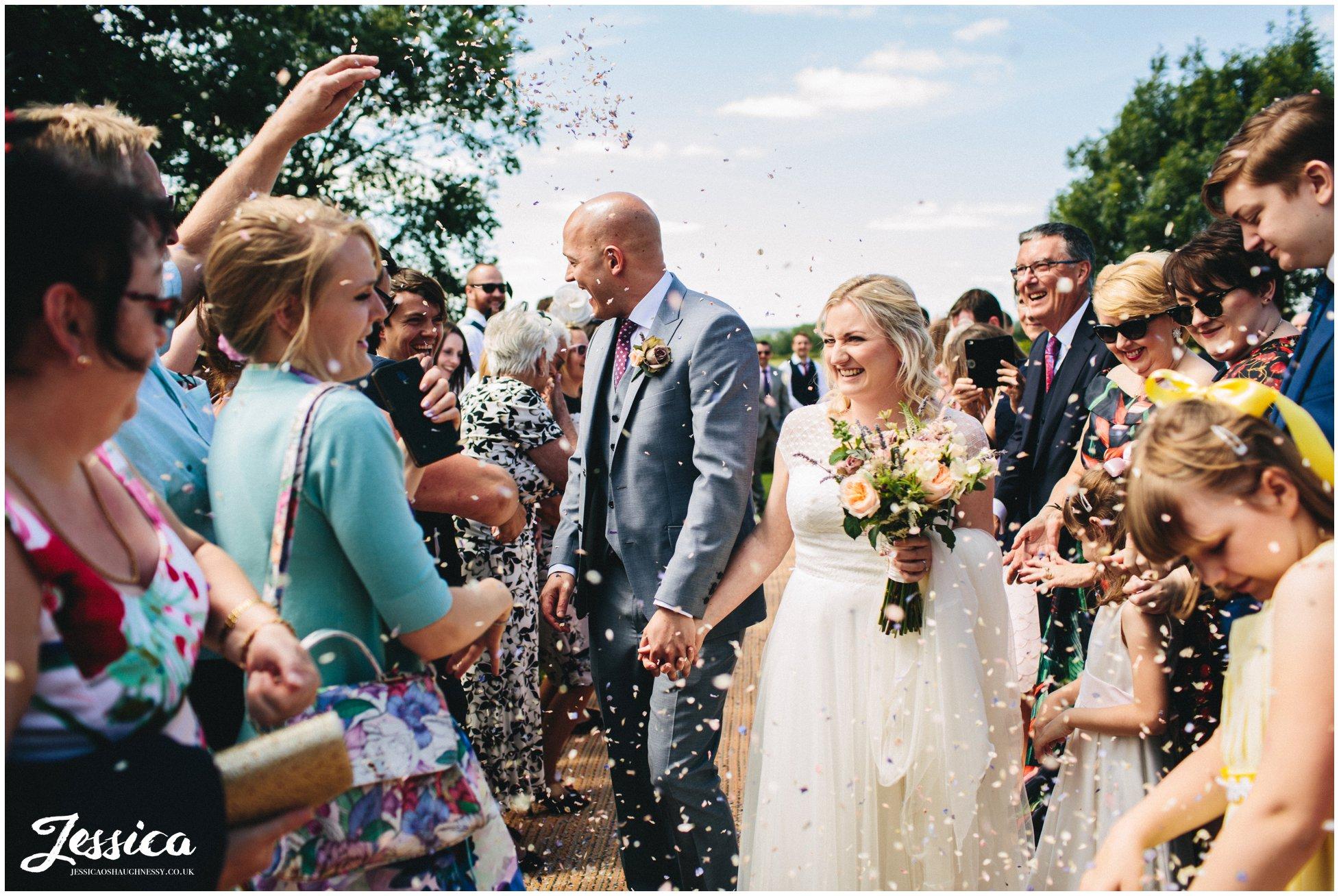 bride & groom walk through the confetti line
