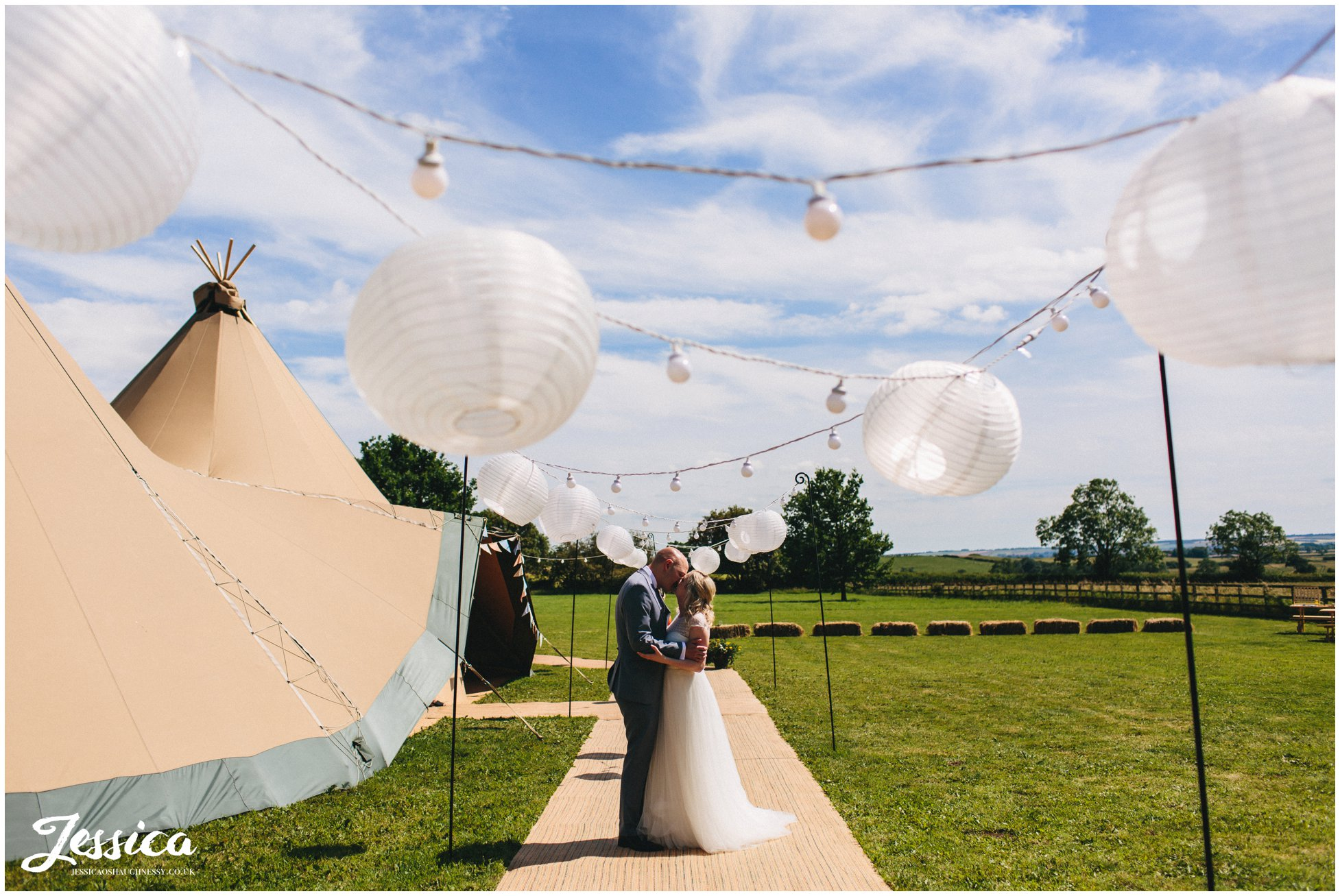 bride and groom kiss under paper lanterns - tipi wedding photography