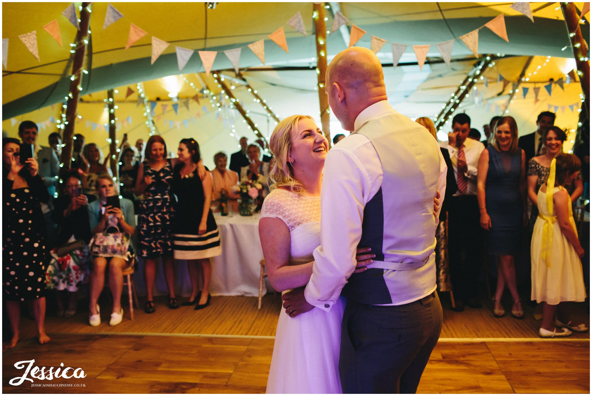 bride and groom share their first dance in the tipi