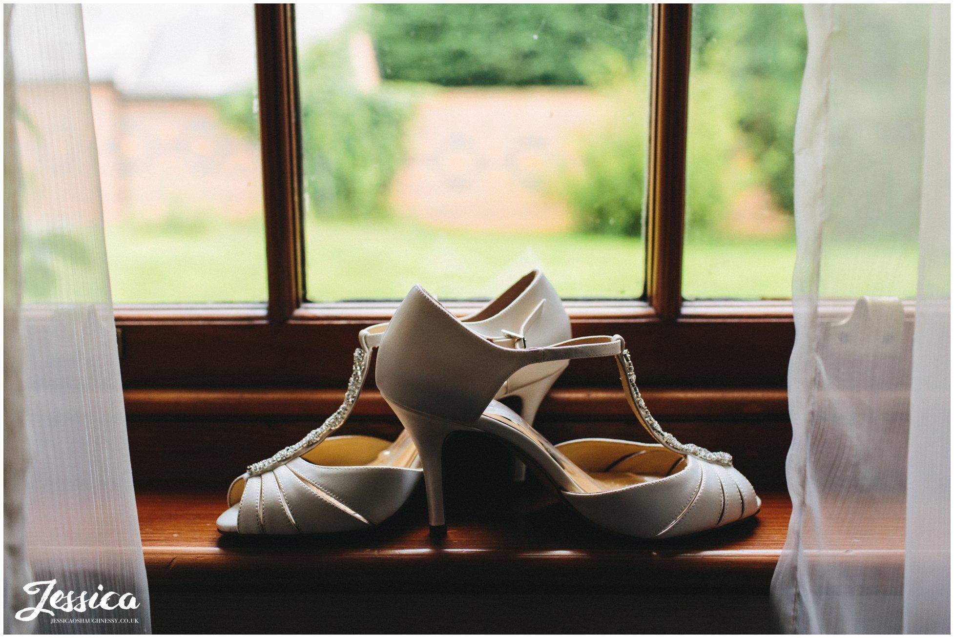brides wedding shoes on windowsil
