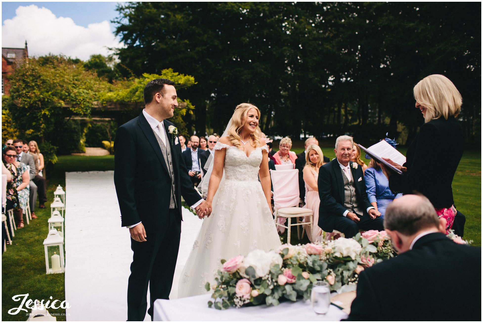 bride & groom hold hands during their cheshire wedding ceremony