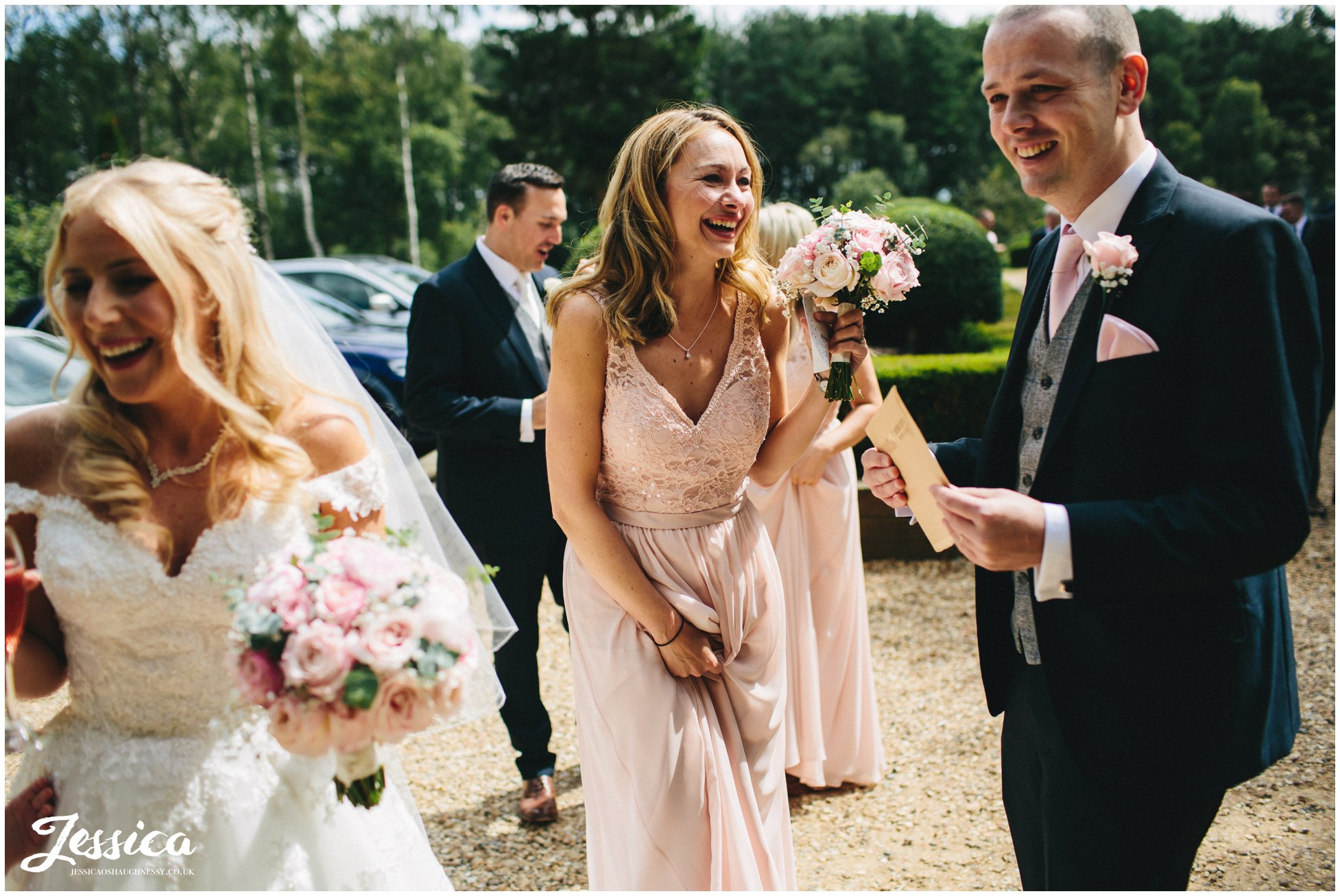 bridesmaid laughing after the nunsmere hall wedding ceremony in cheshire