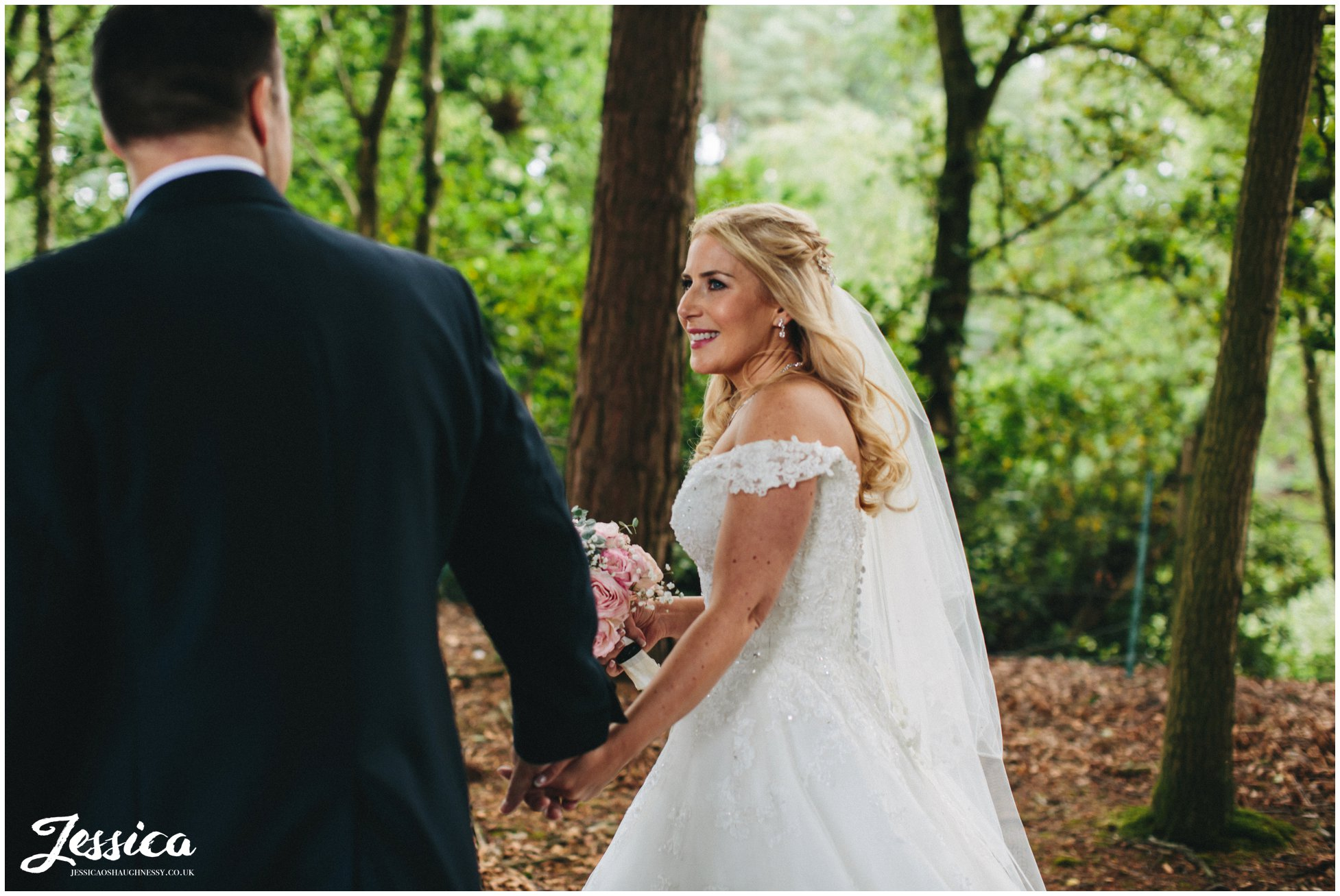 newly wed's holding hands in the forest - a cheshire wedding