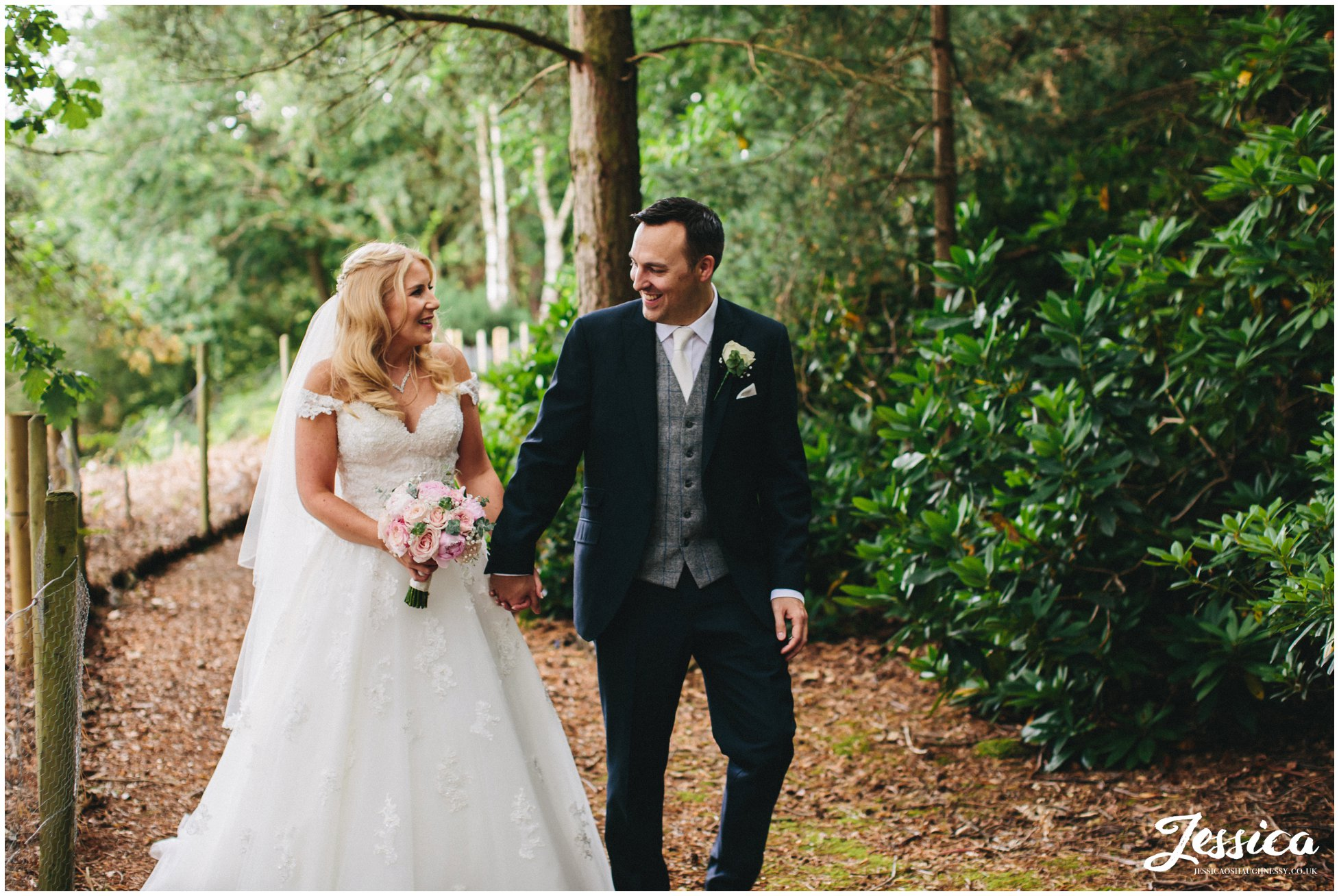 bride & groom walking through trees at their wedding in cheshire