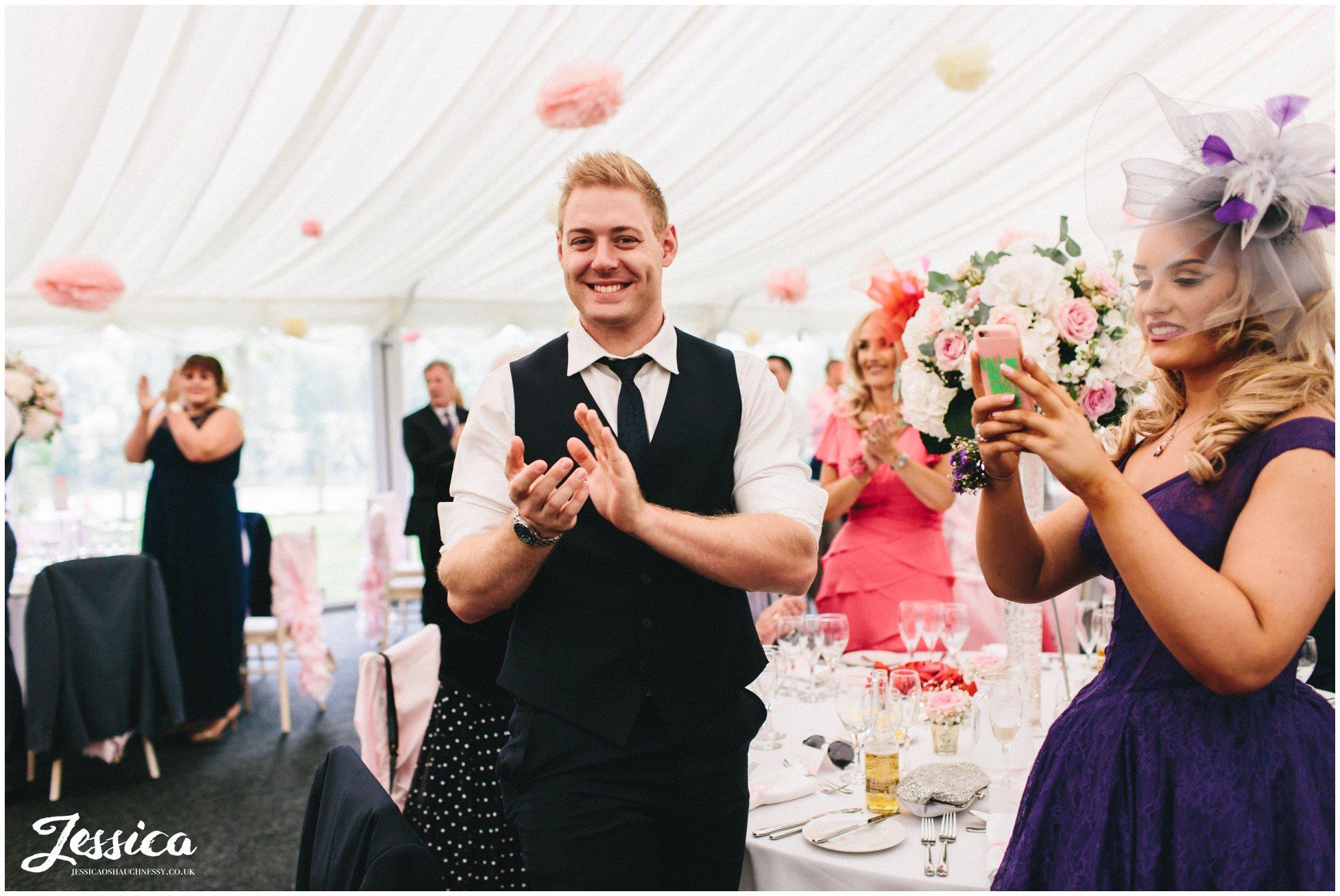 wedding guests clap as bride & groom enter