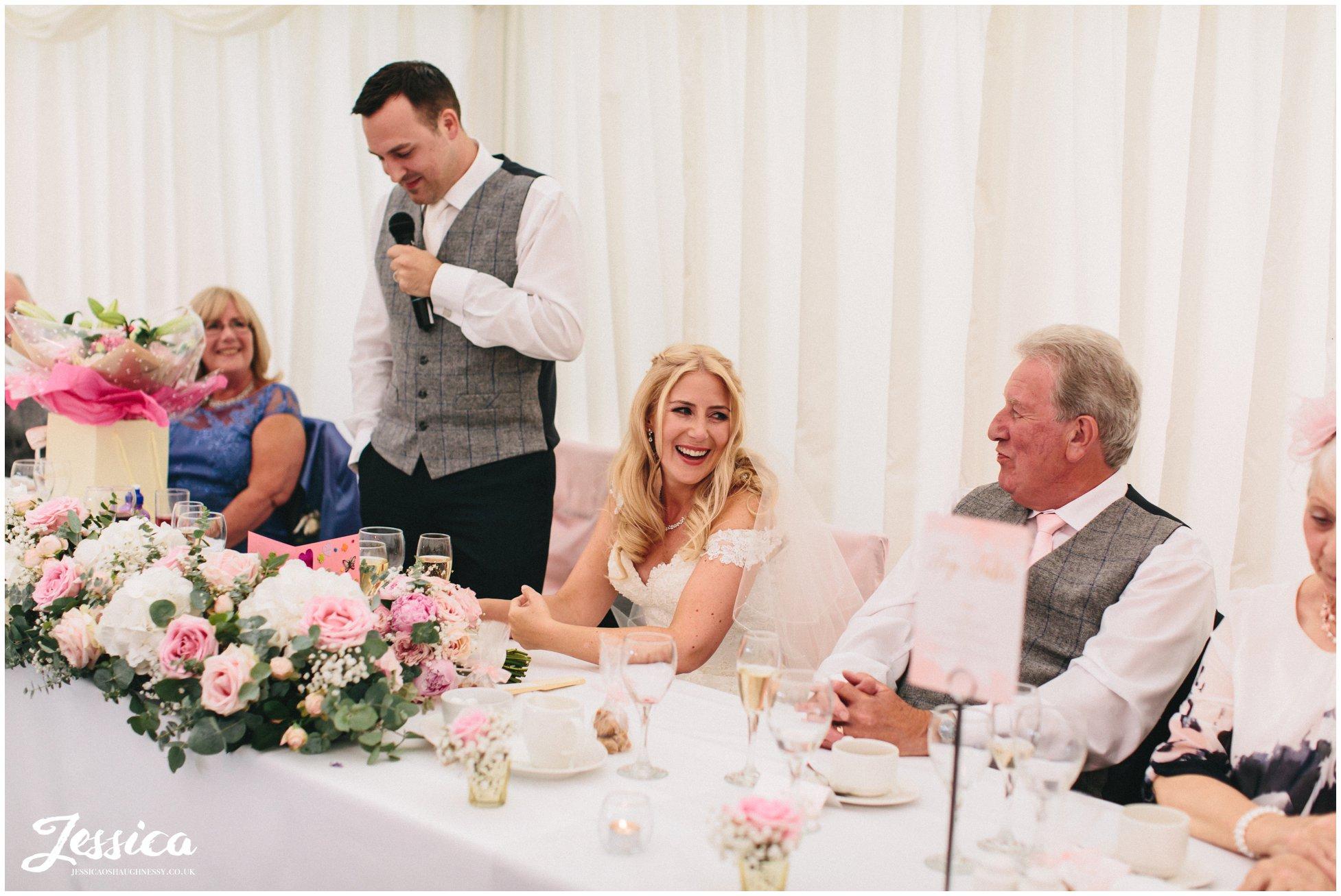 bride enjoying groom's speech at her wedding in nunsmere hall, cheshire