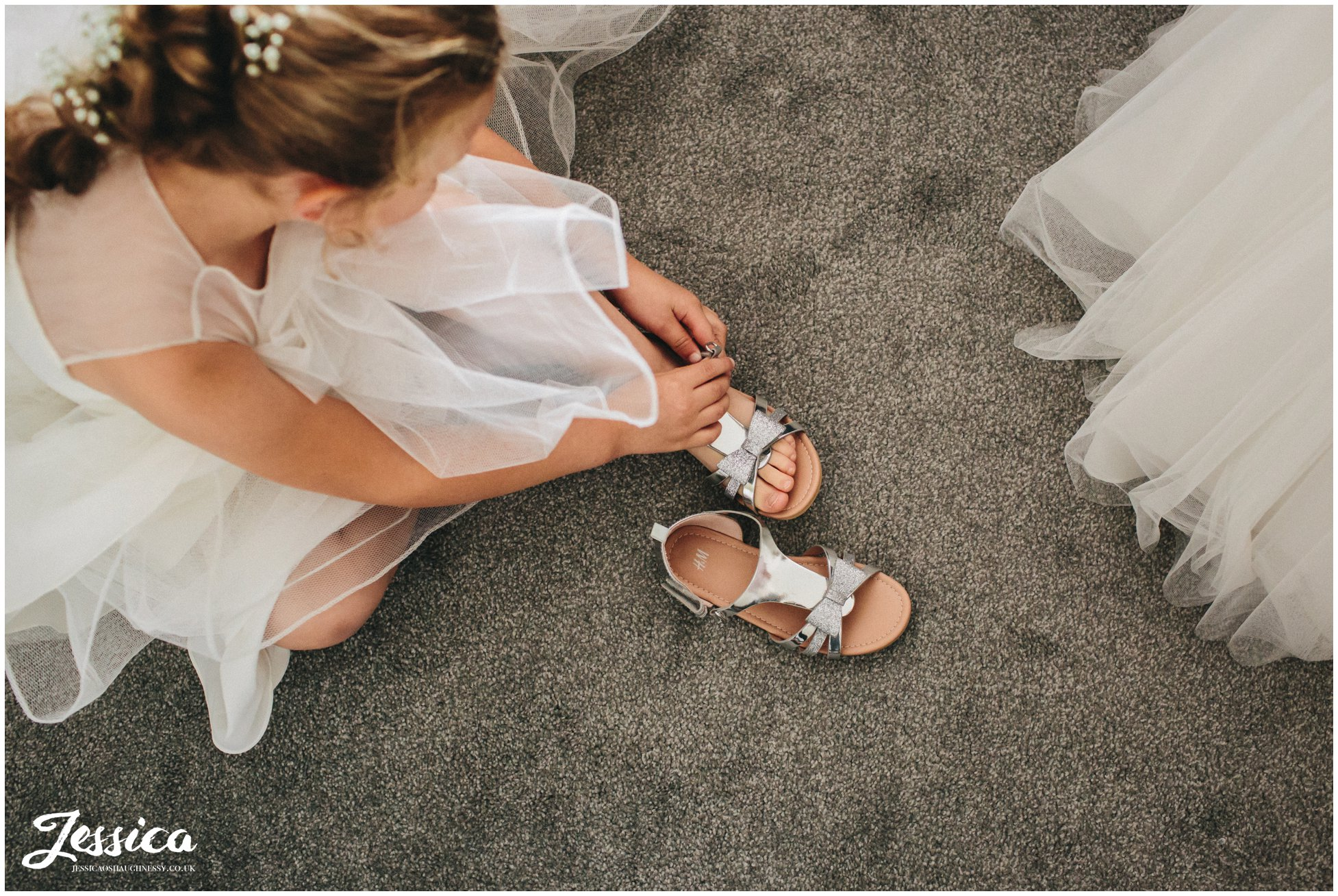 flower girl puts on her shoes - sheldrakes wedding photography
