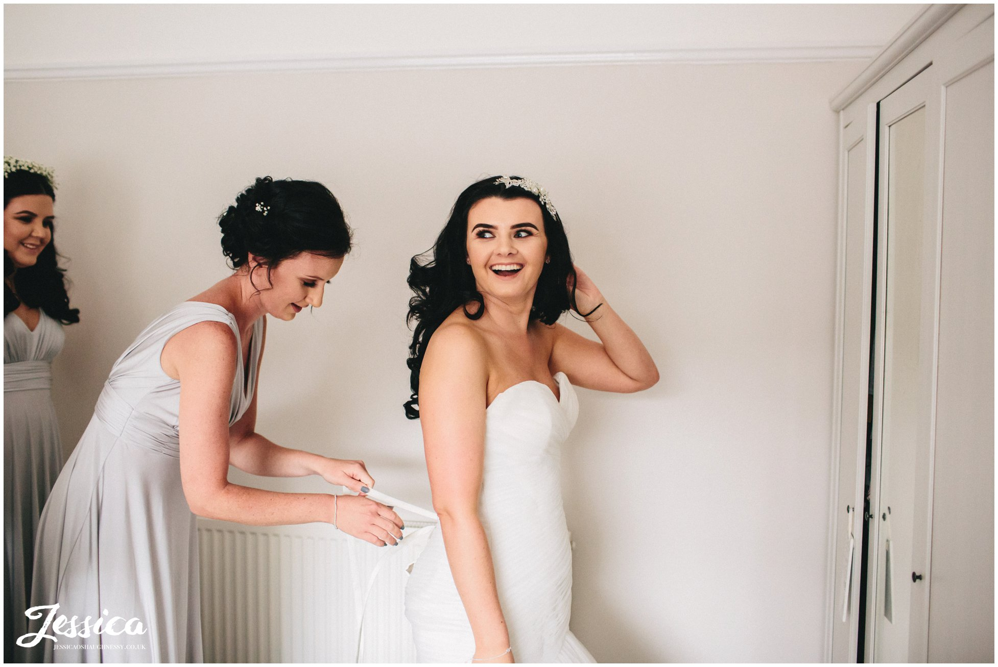 bride gets into her wedding dress with help from bridesmaids