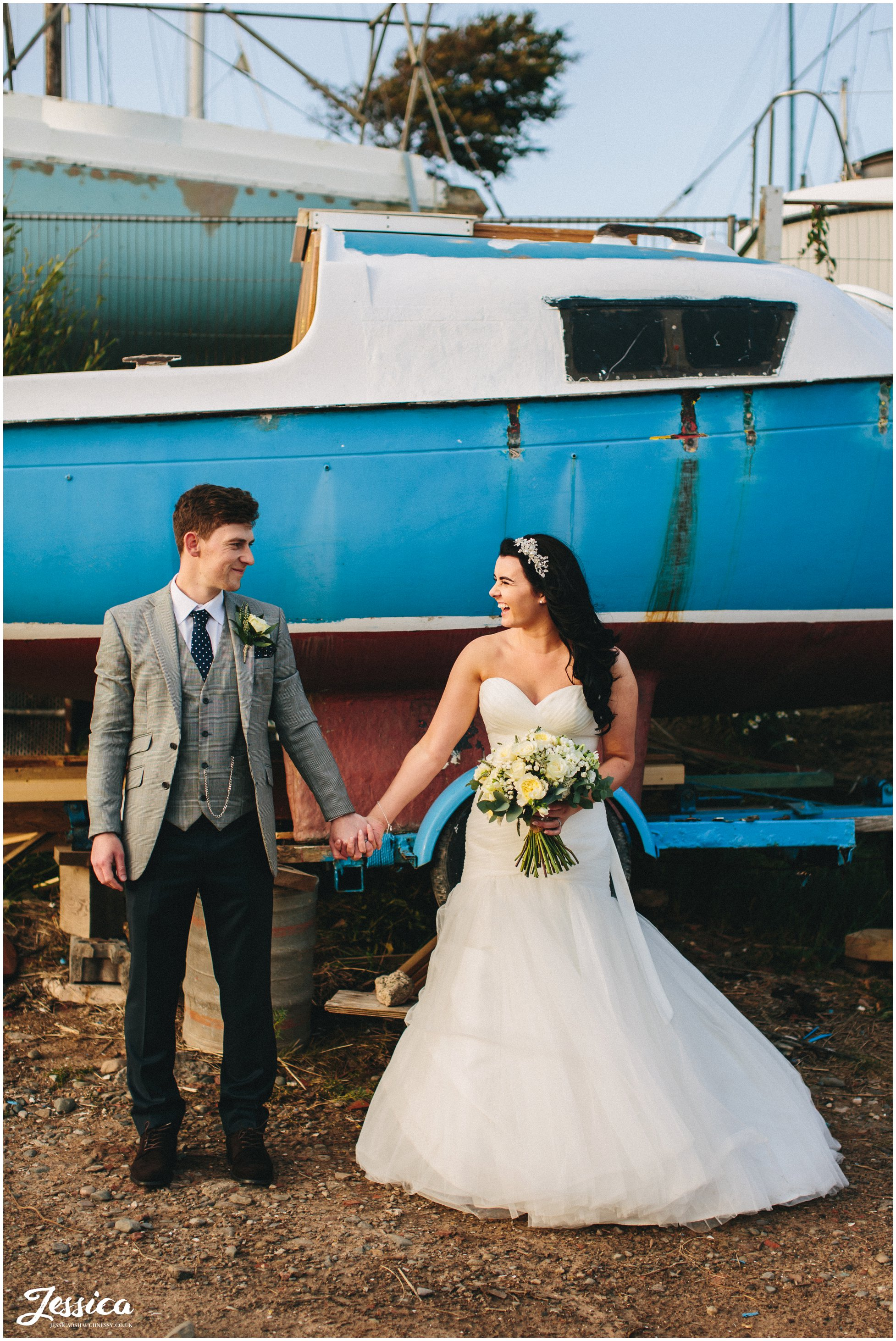 newly wed's hold hands in front of a boat