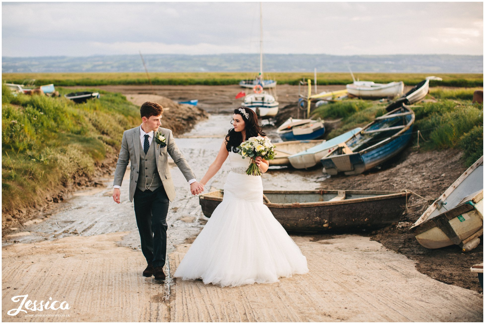 bride & groom walk hand in hand by boats