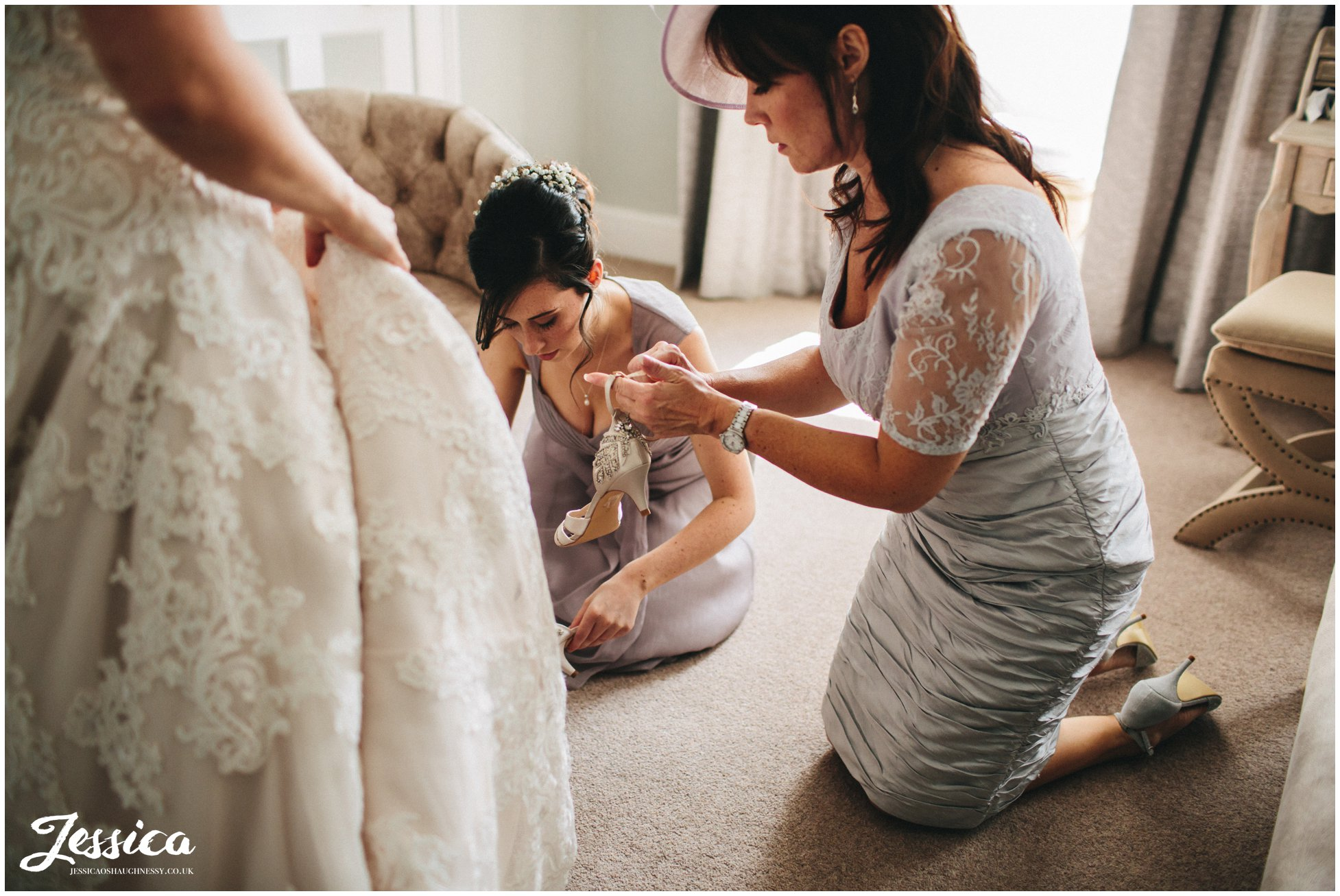 mother of the bride putting the brides shoes on