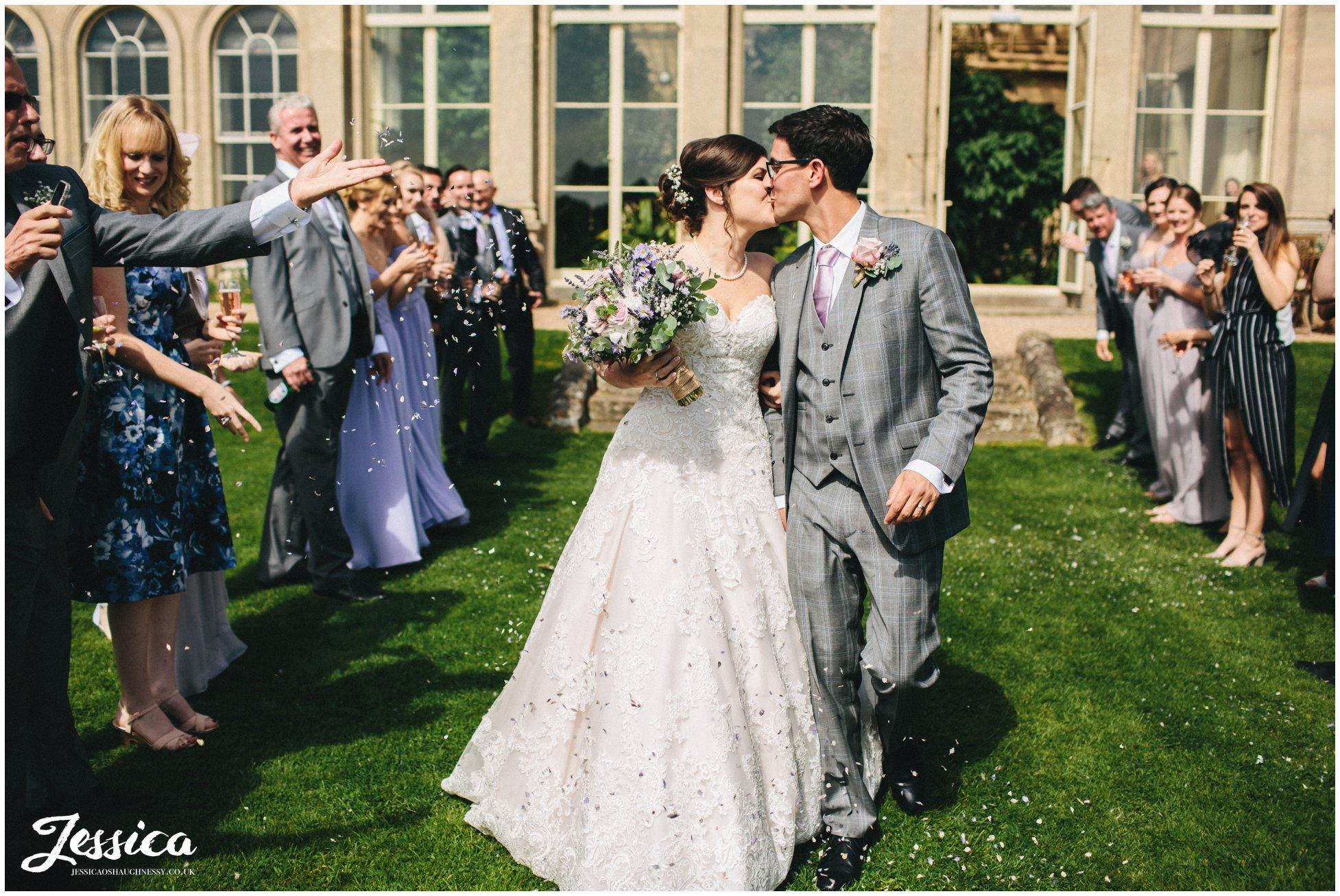 bride & groom kiss during confetti line